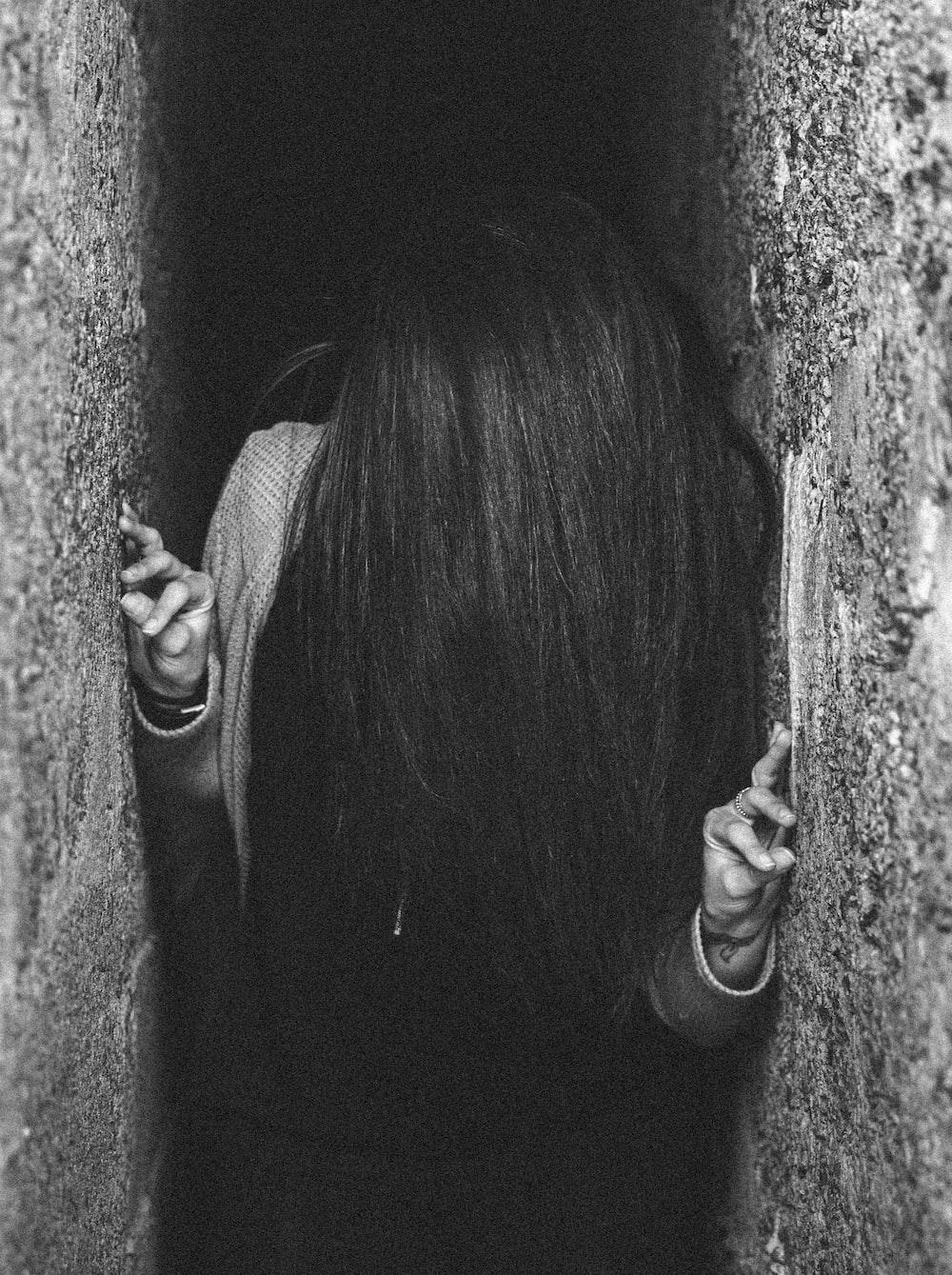 woman between gray concrete wall
