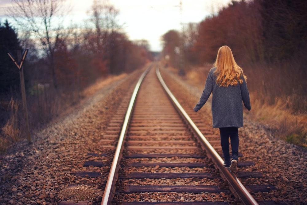 woman walking on rail road