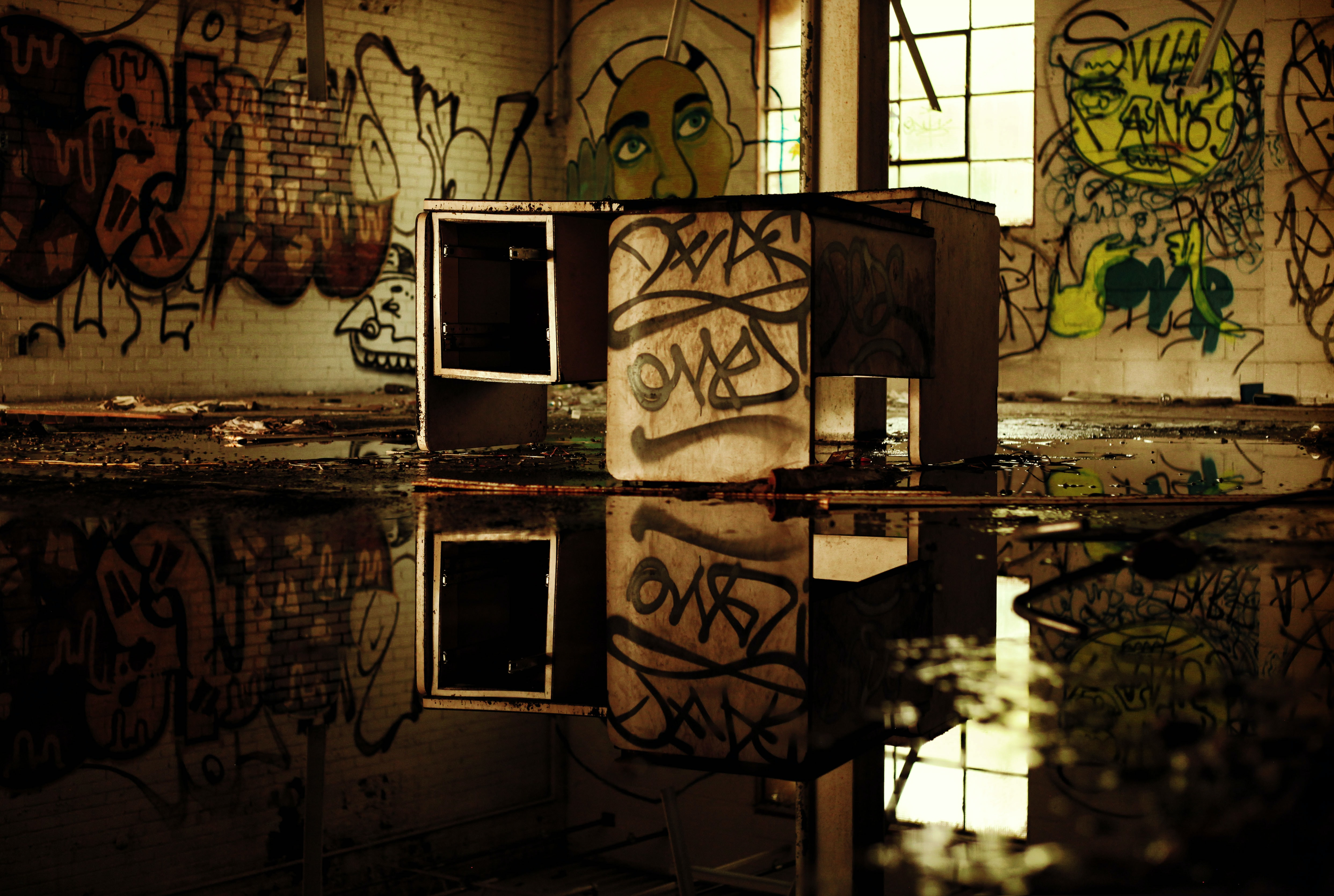 A dilapidated desk on a wet floor in an abandoned building with graffiti on its walls