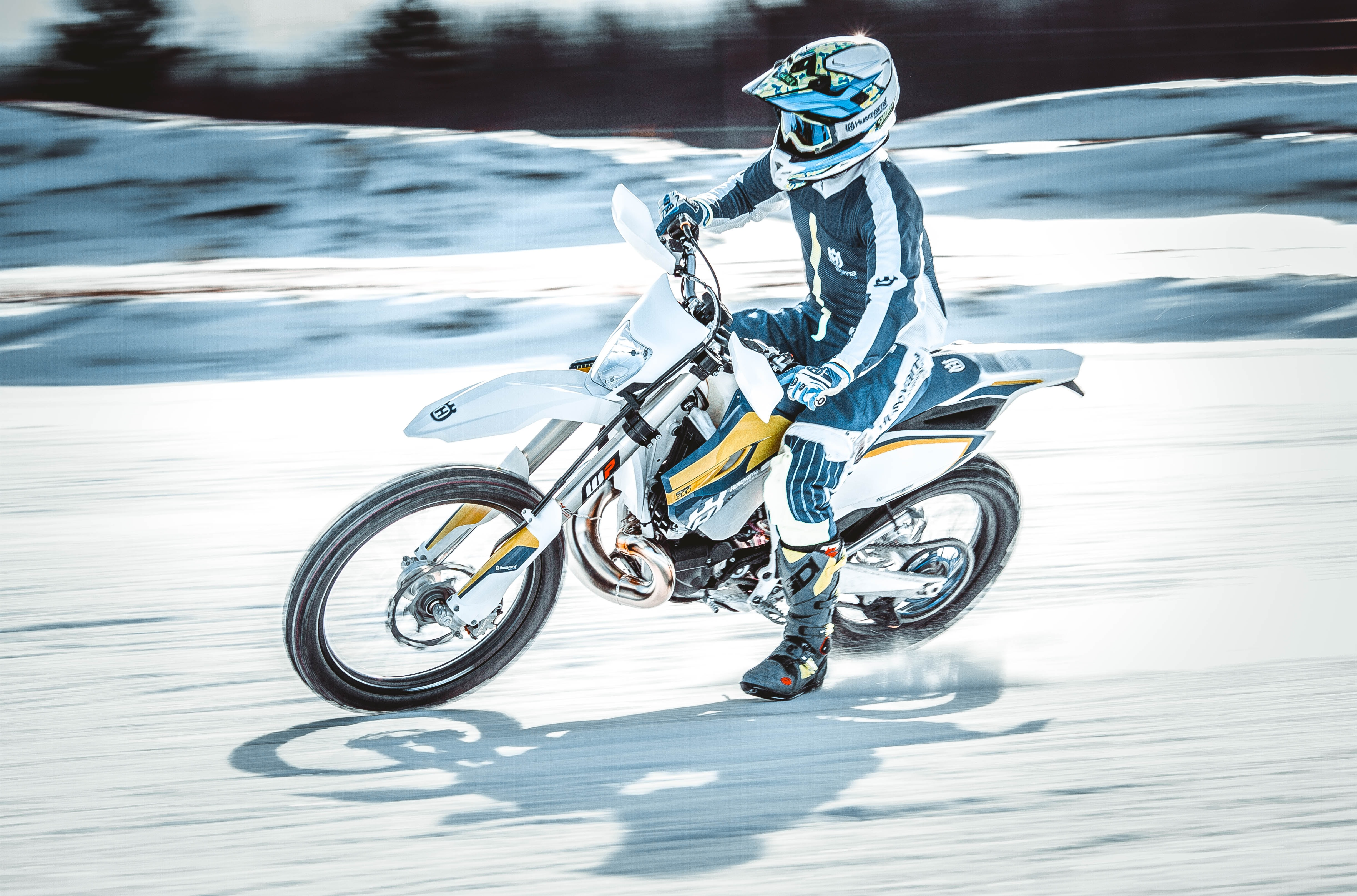 person riding on black and white motocross dirt bike