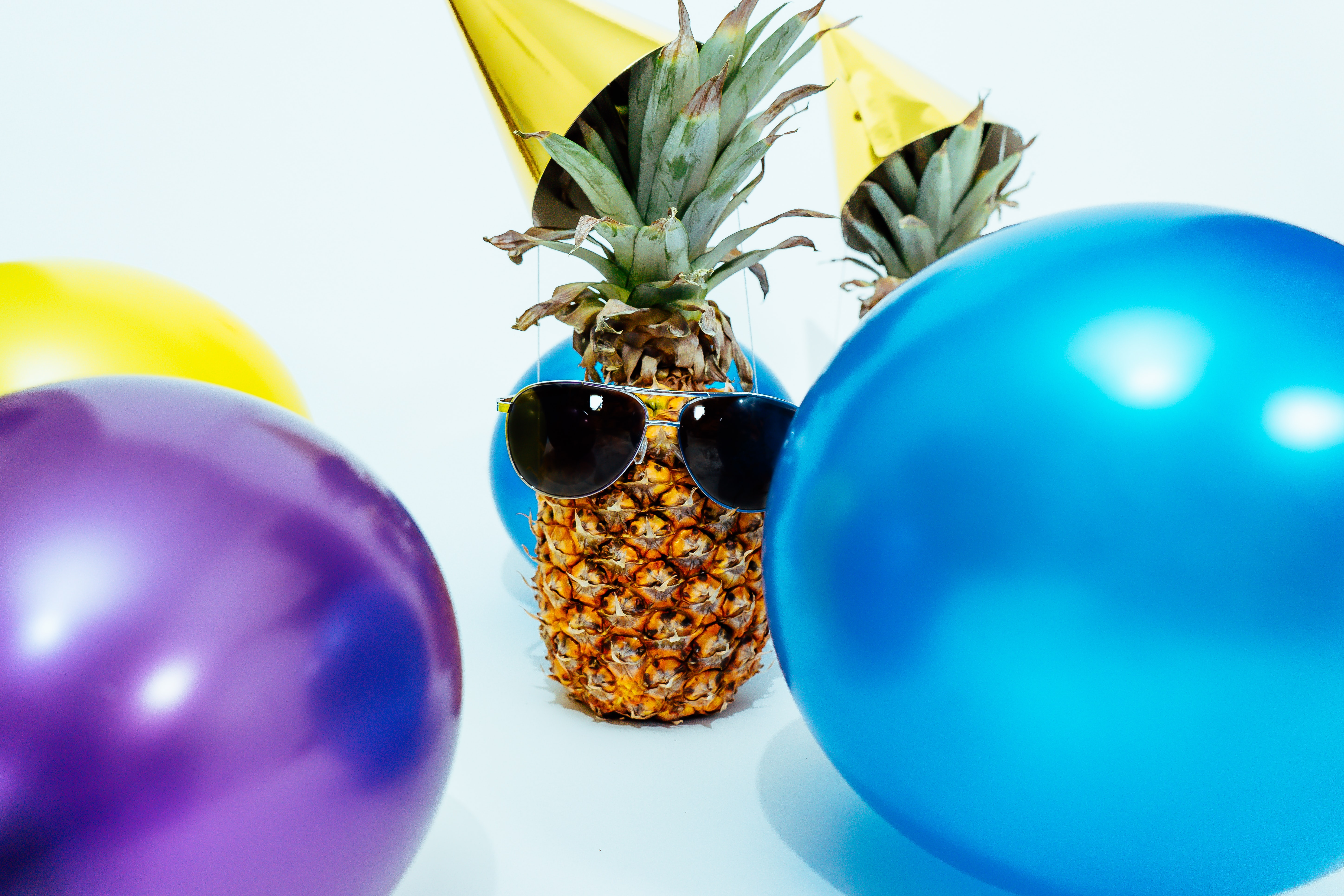A pineapple wearing sunglasses and a party hat.