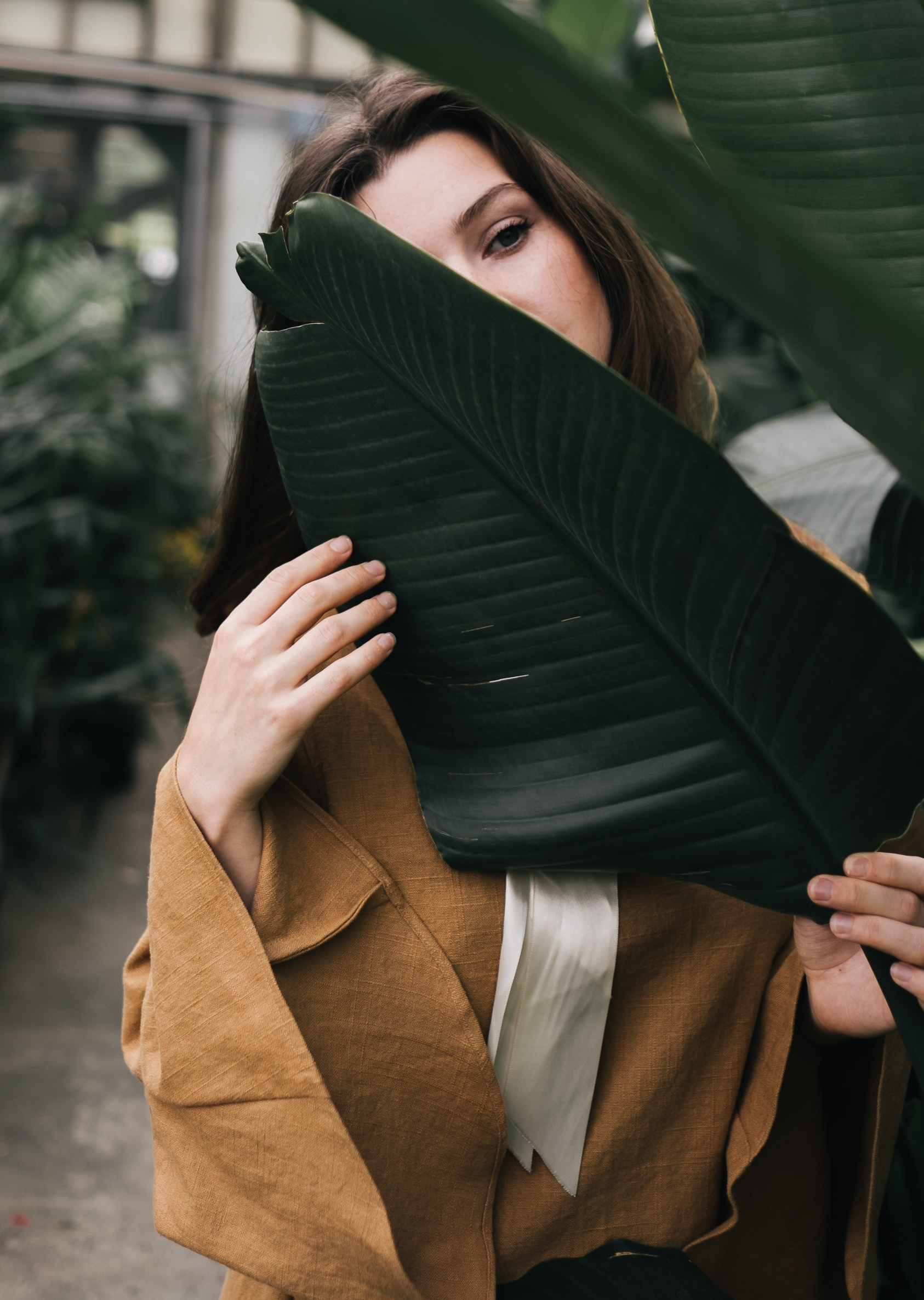 A brunette woman holding a large dark green leaf in front of her chest