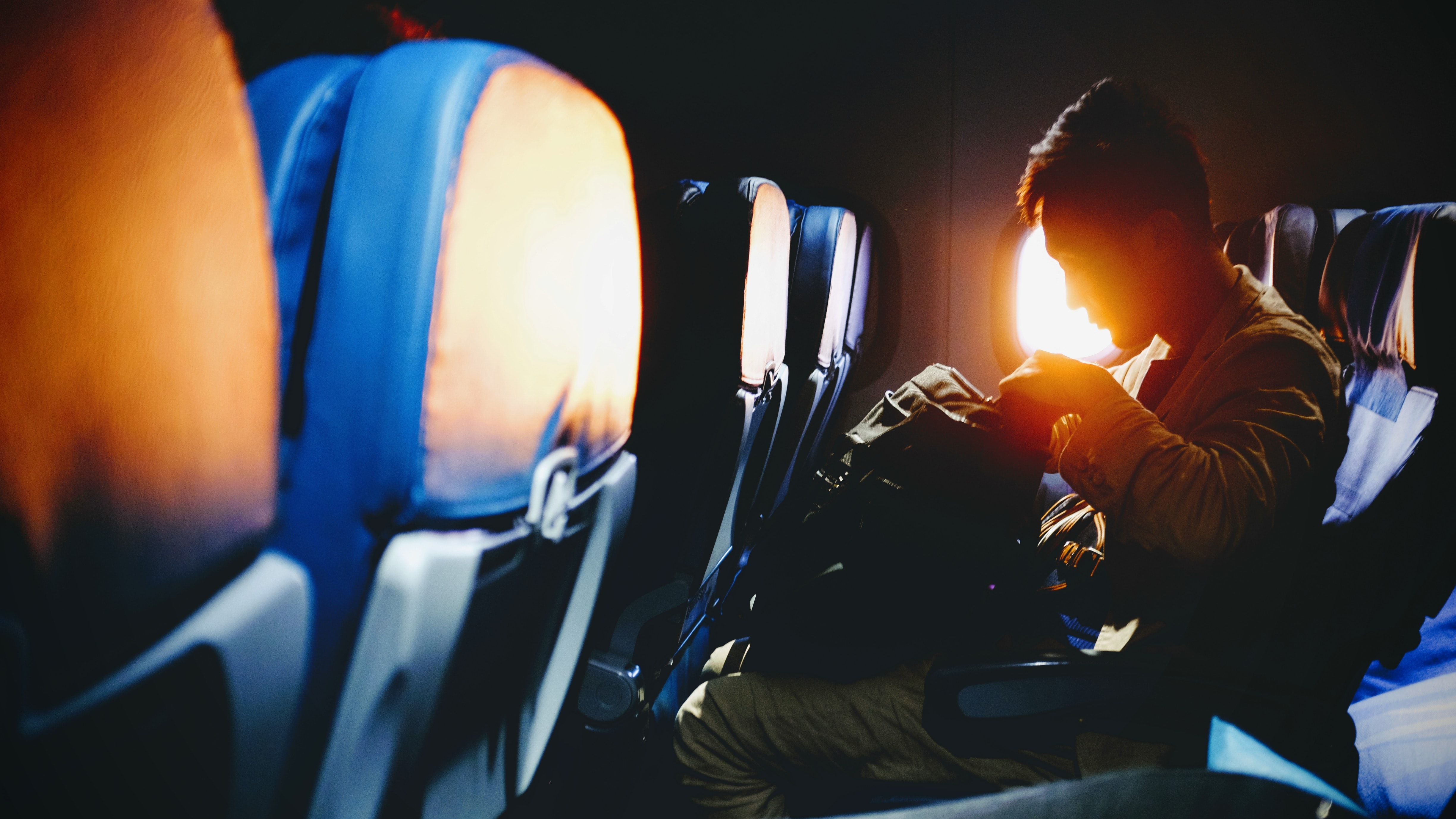 A man in an airplane seat looking into his backpack as setting sun shines through the window