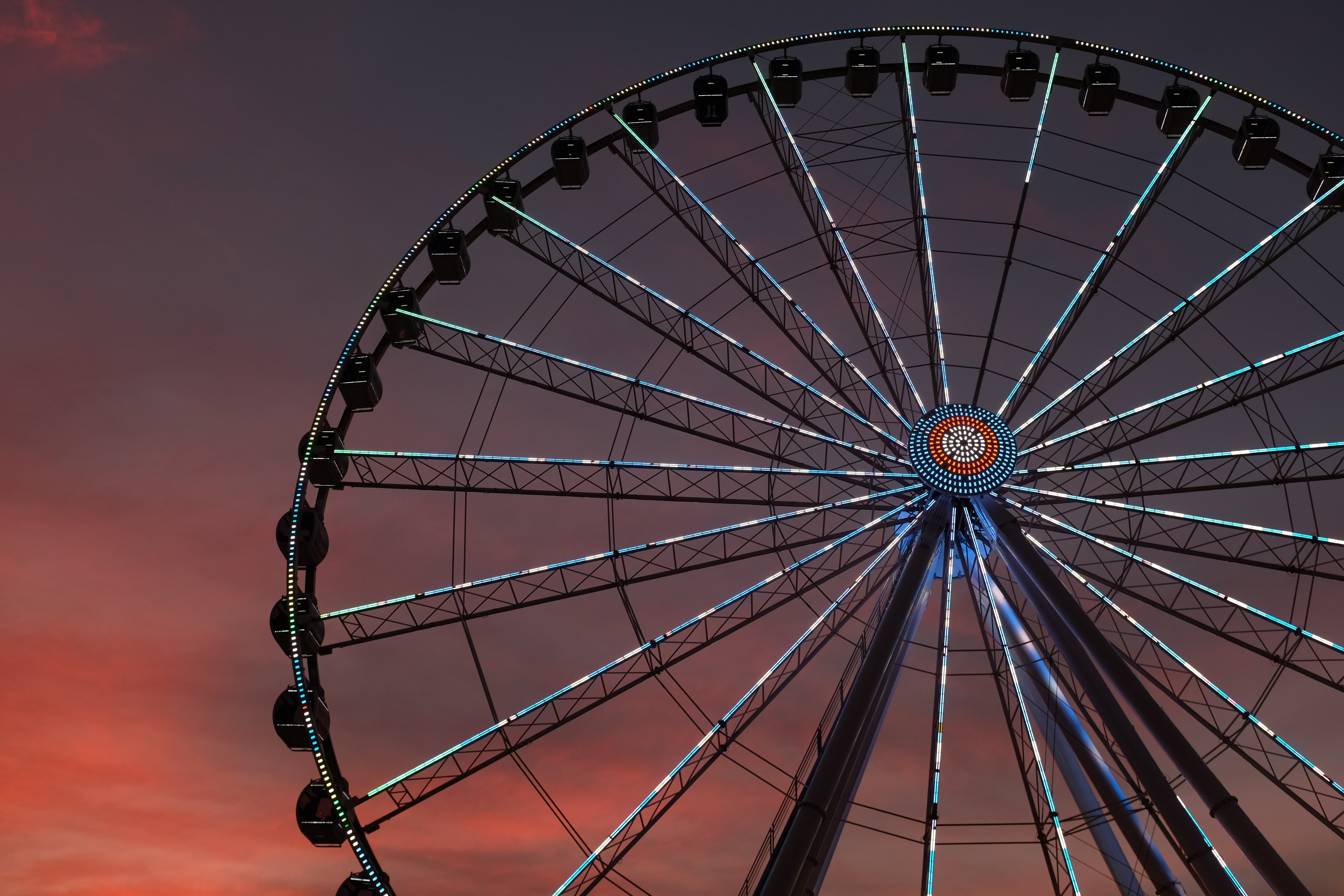 Carnival ferris wheel with blue lights against an evening sunset