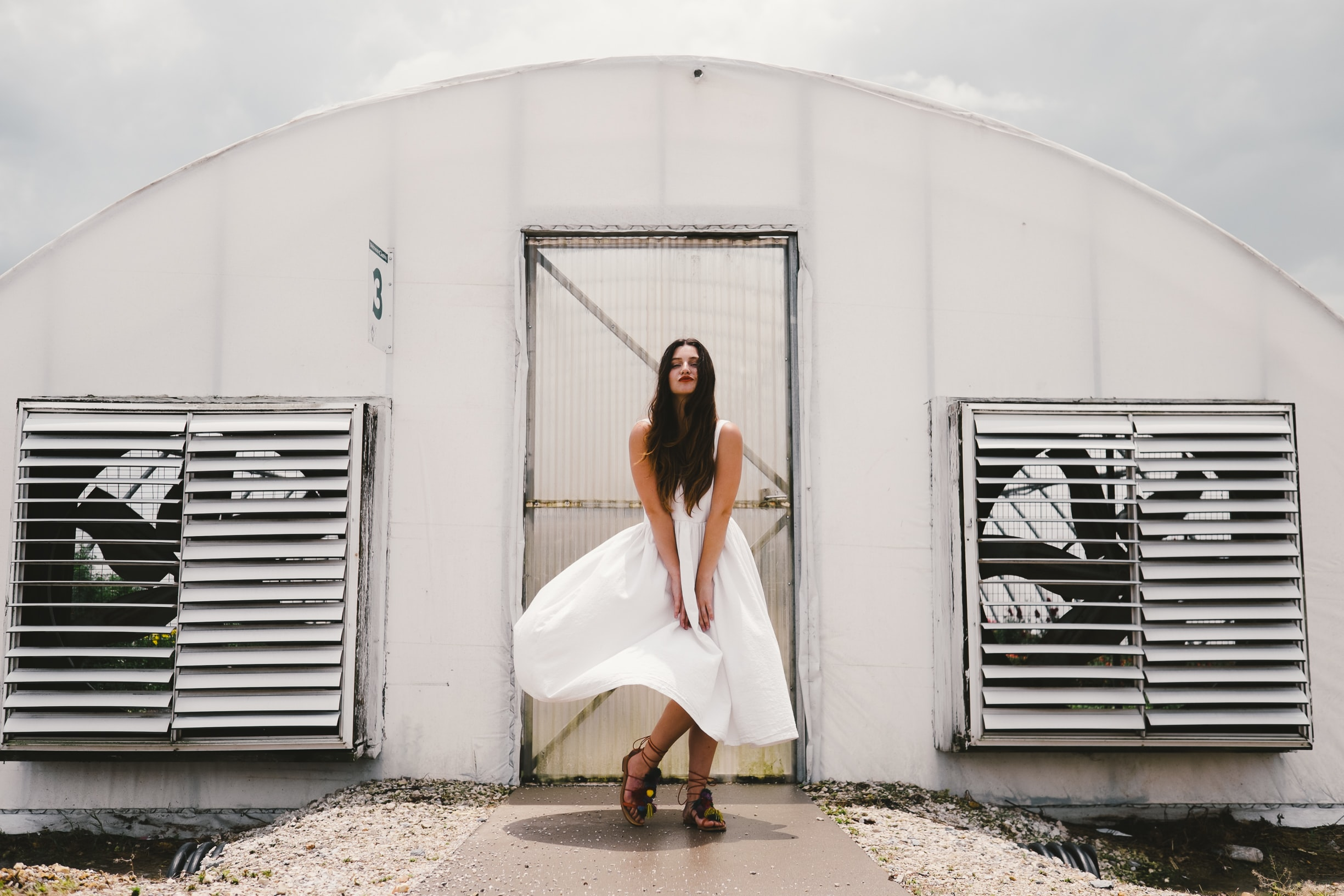 woman wearing white dress standing in front of white enclosure during daytime