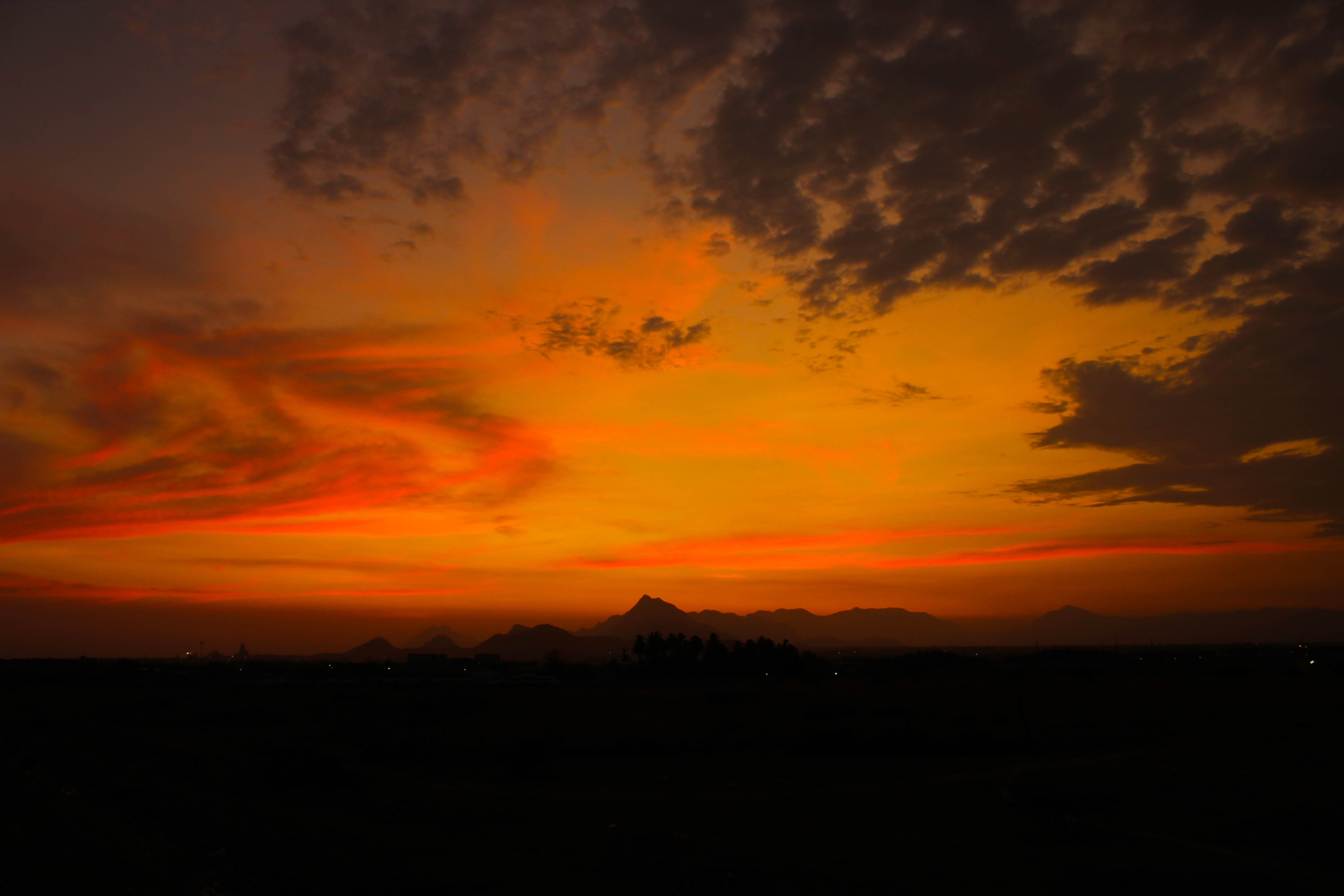 Swirling clouds in a reg and orange sunset sky, with silhouetted mountains in the distance