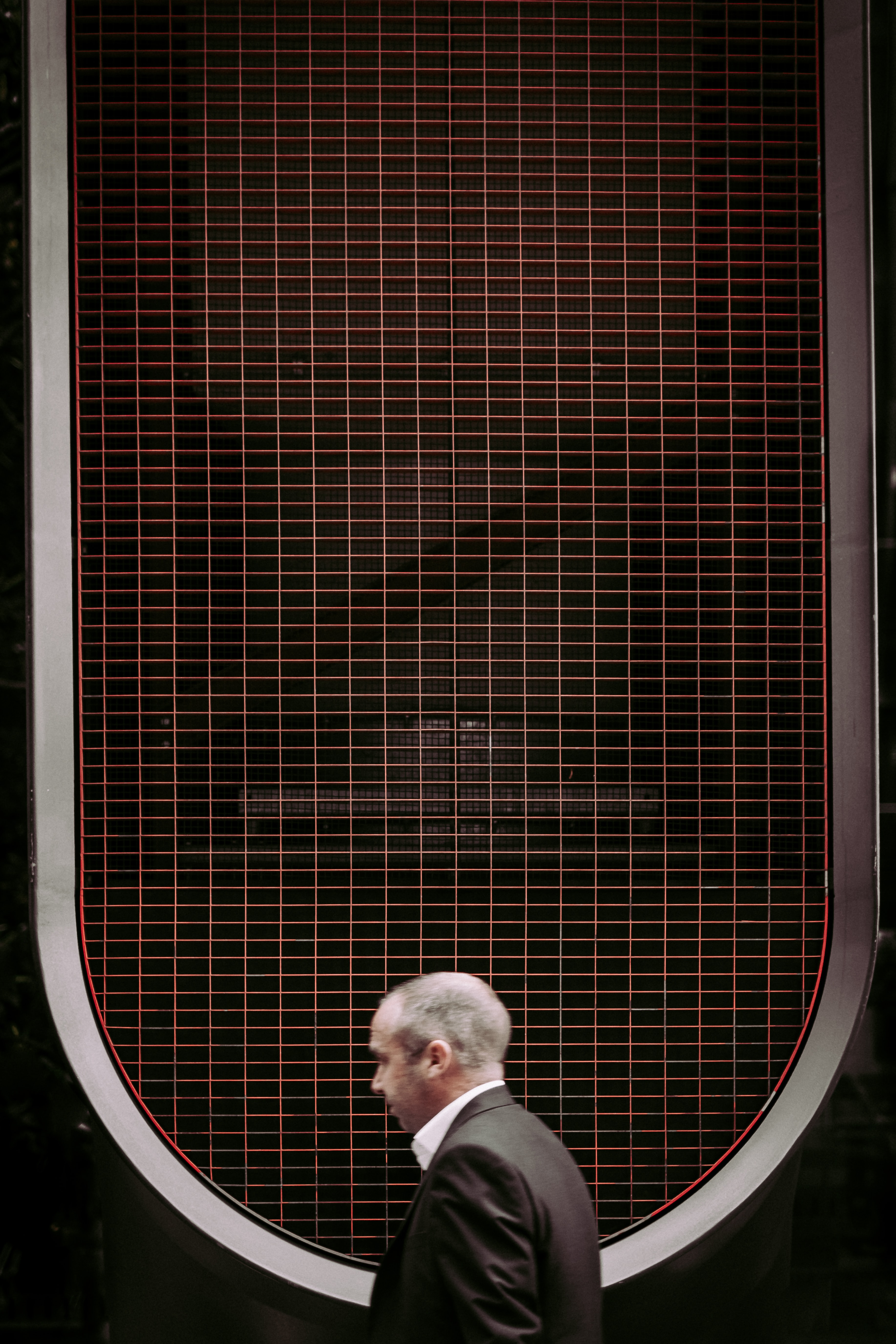 A low-angle shot of a man in a black suit under a grid on the roof