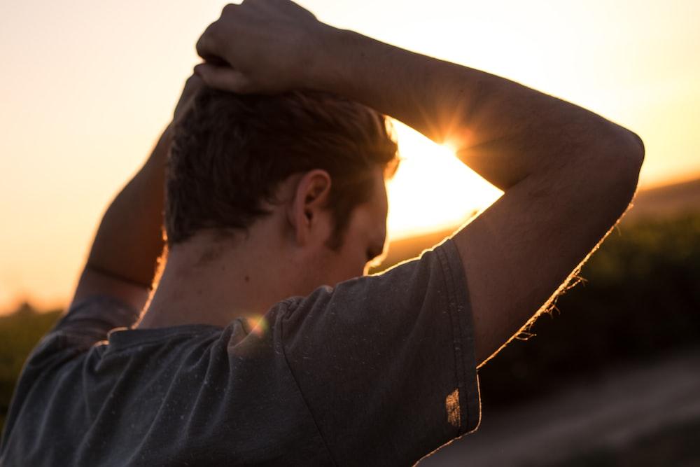 man holding his hair against sunlight