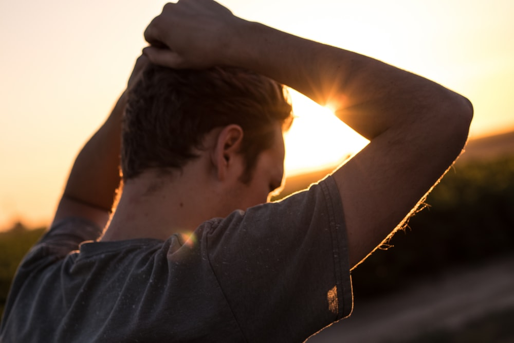man holding his hair against sunlight