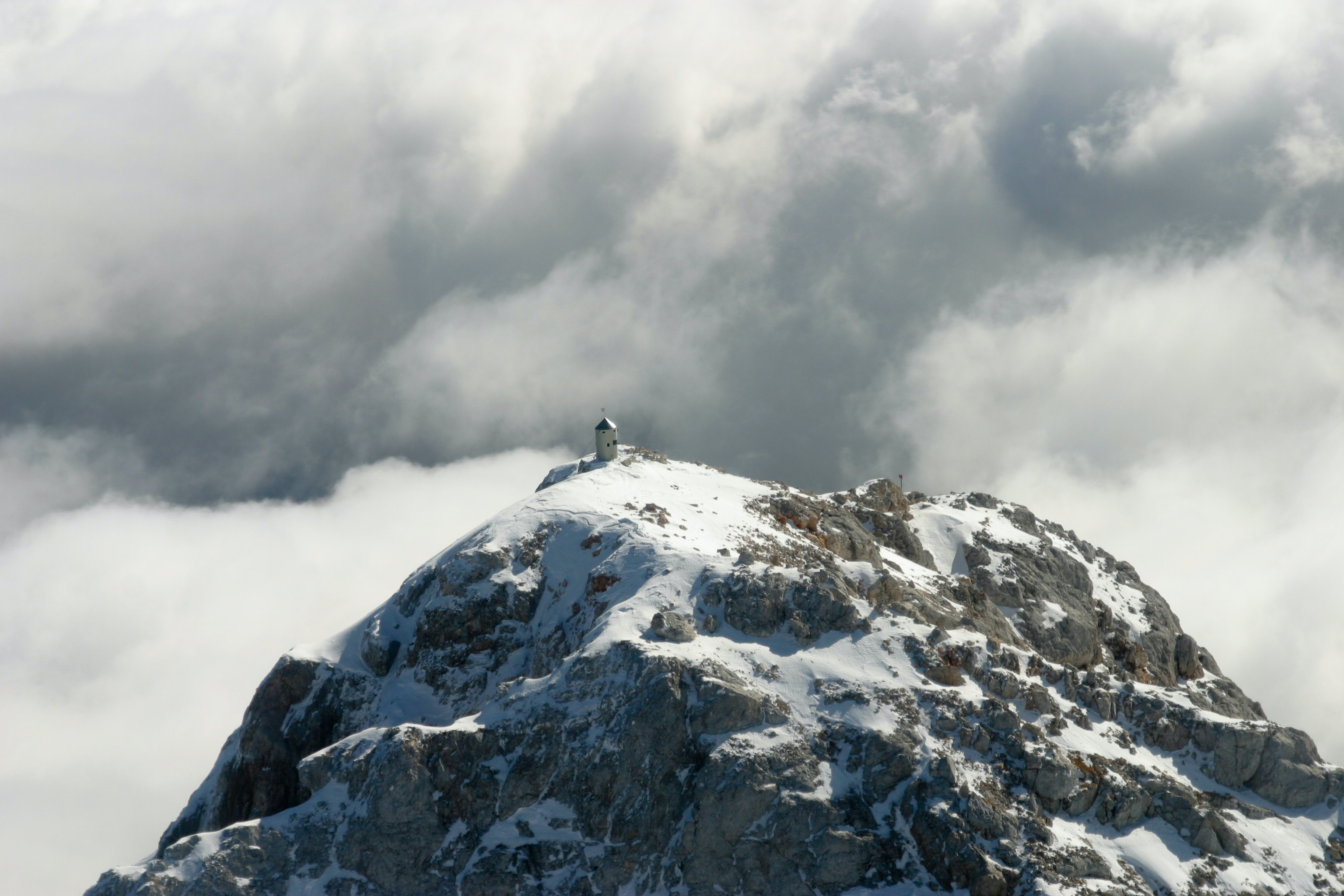 On top of a snow covered mountain with stormy clouds in Triglav.