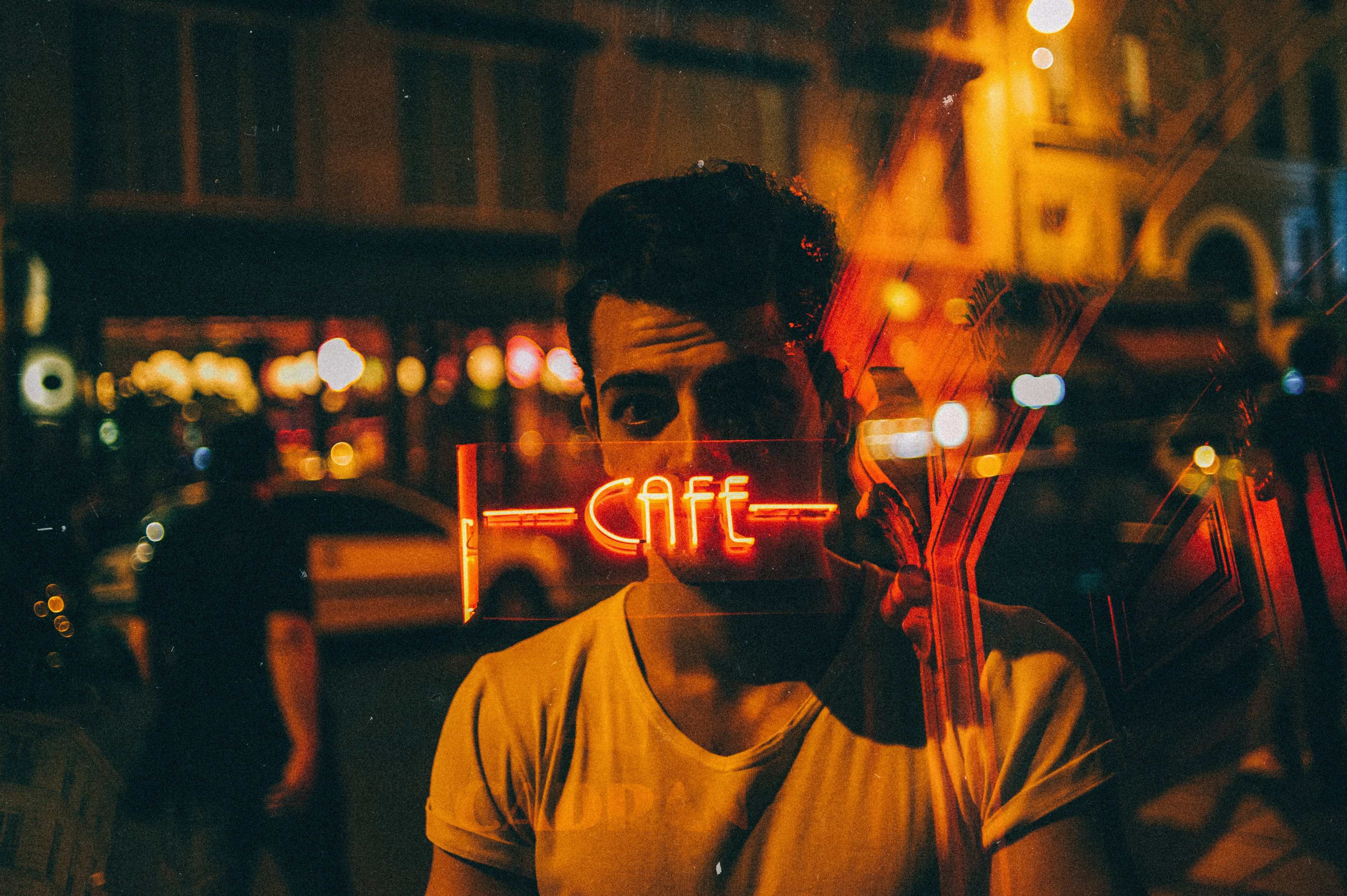 A man standing with a neon cafe sign covering his face in the window reflection