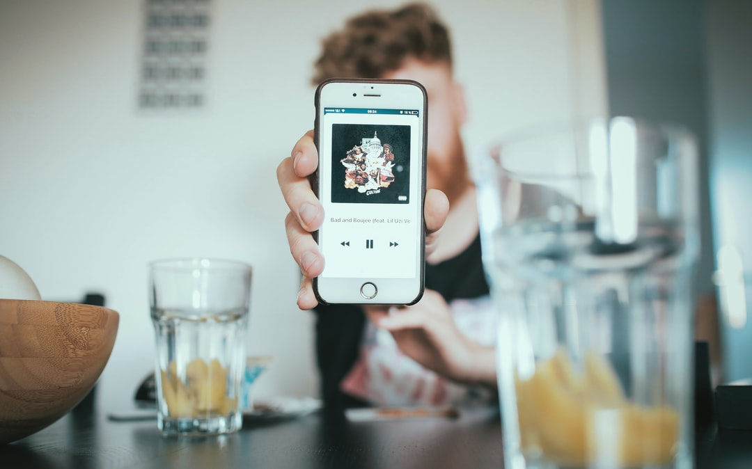 A close-up on an iPhone screen with a music app in the outstretched hand of a bearded man