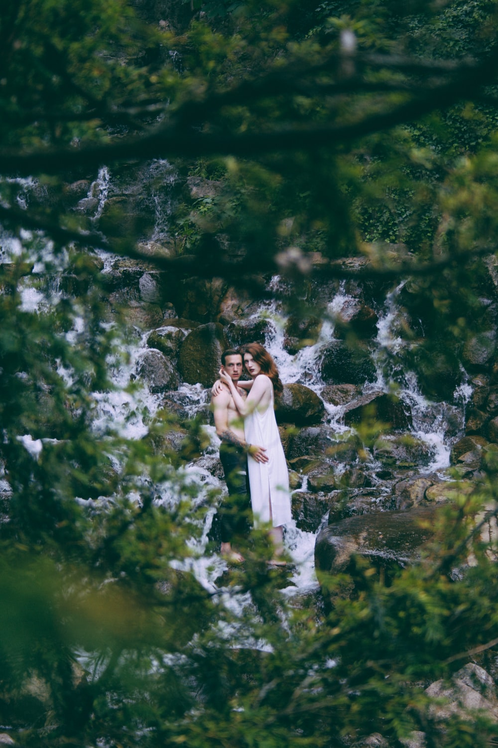 man and woman hugging on running water surrounded by rocks