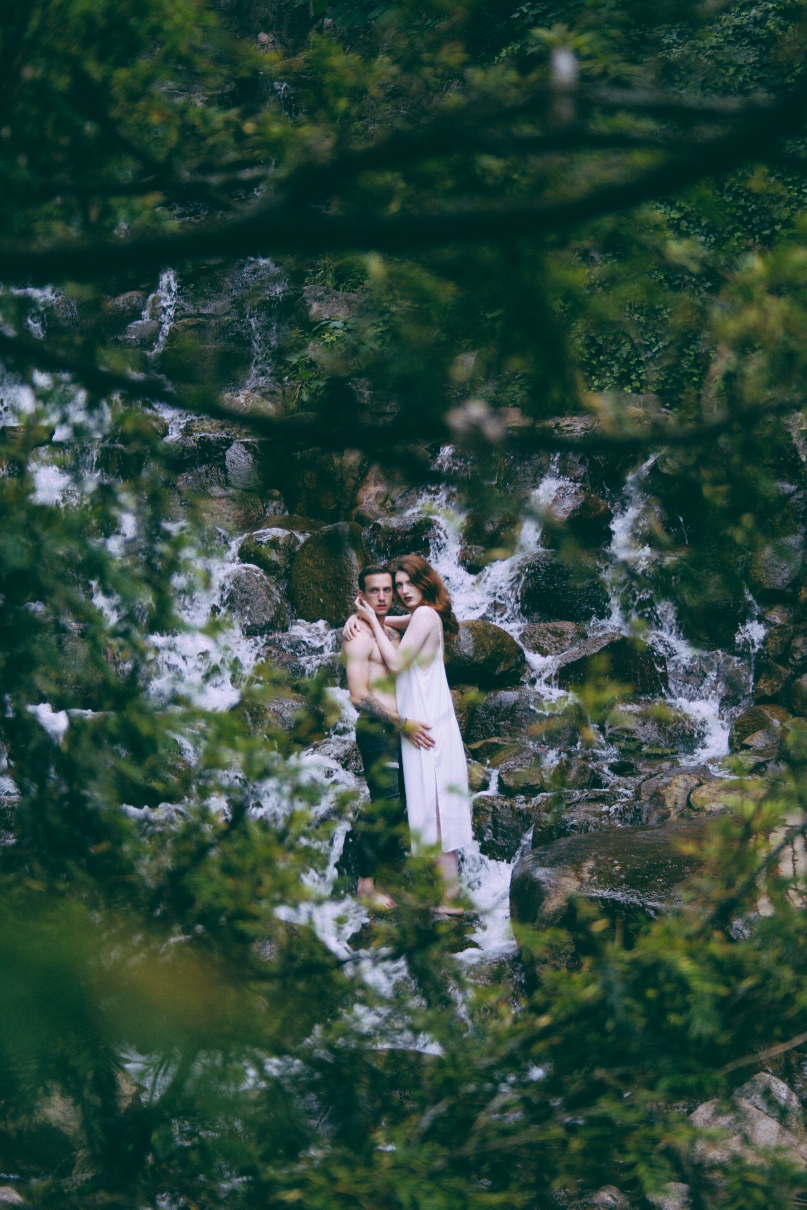 A shirtless man and a woman in a dress embrace near a waterfall in the woods.