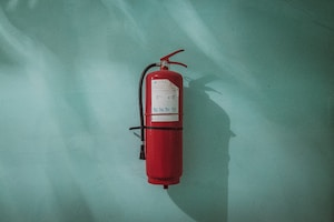 Hard and soft facilities management red fire extinguisher on green wall