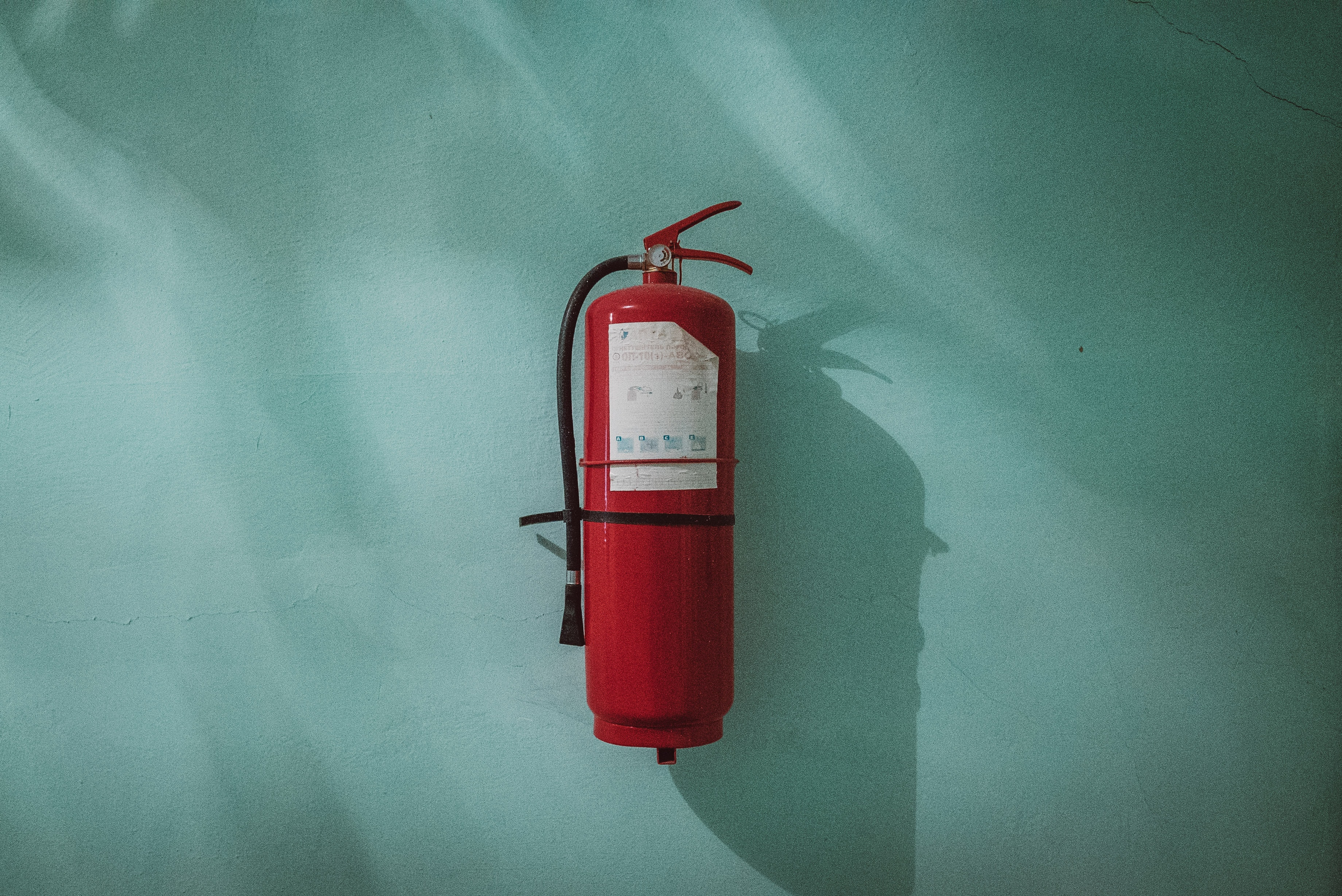 red fire extinguisher on green wall