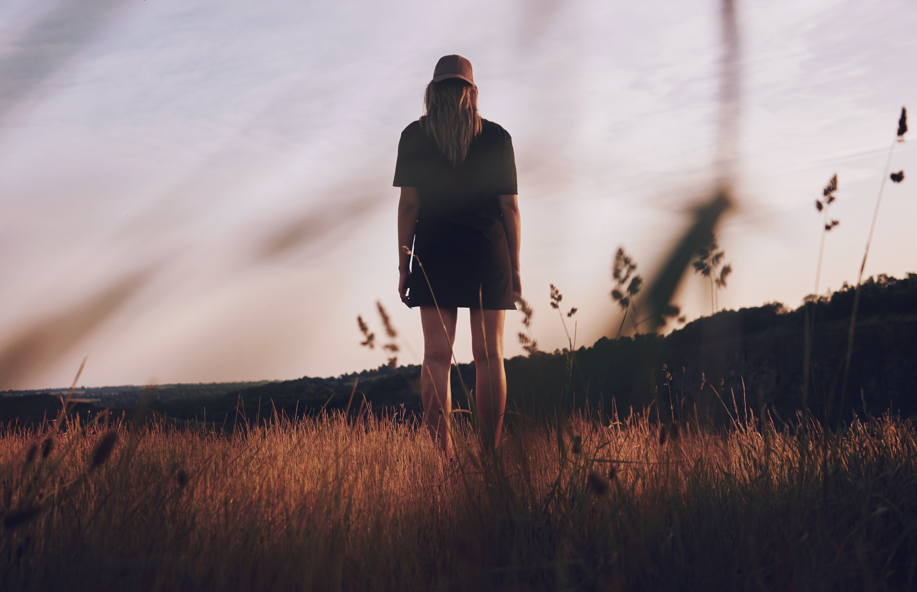 worm's view photography of woman standing on grass field