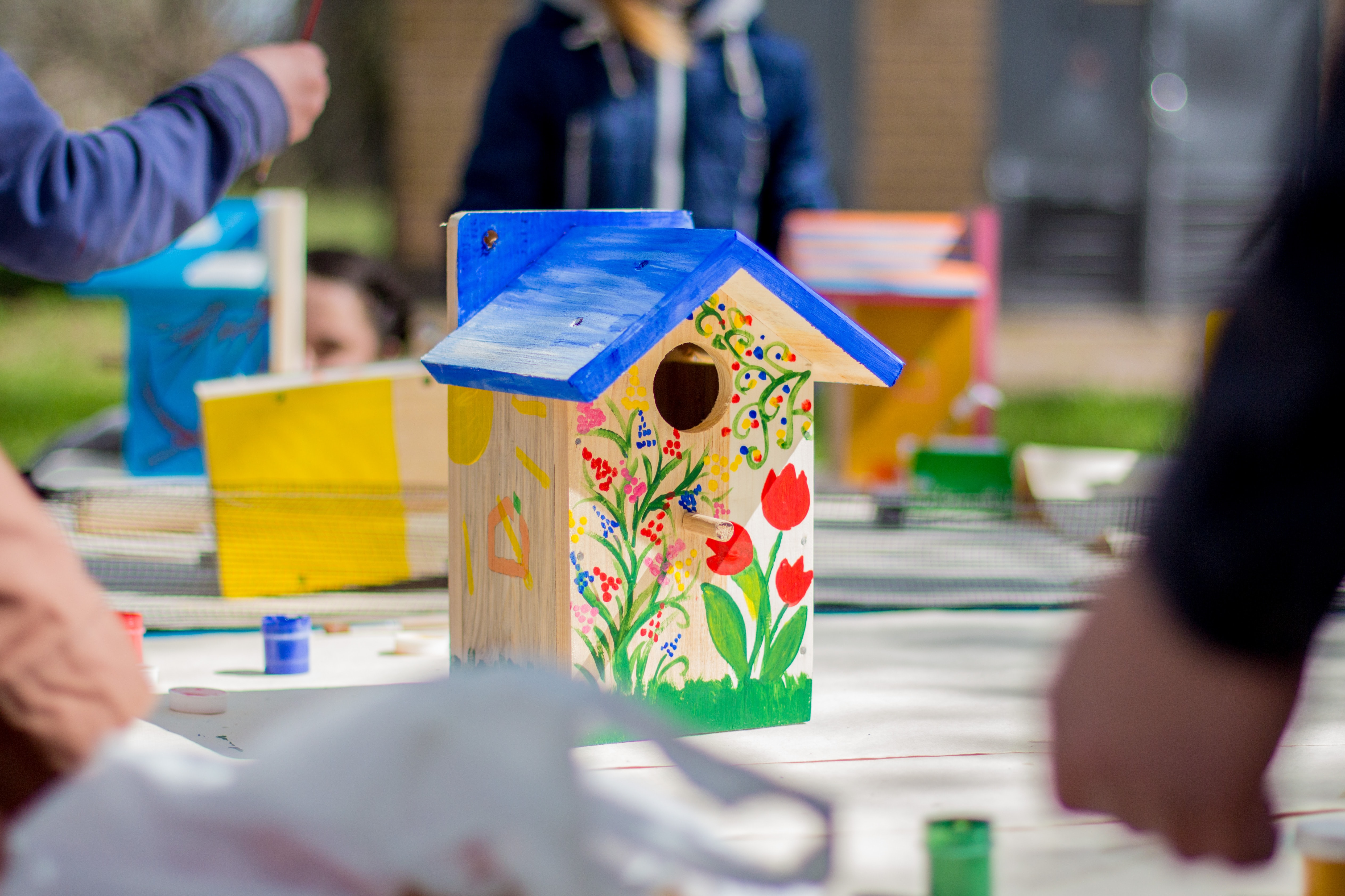 People decorate a birdhouse with paint at a DIY arts and crafts event