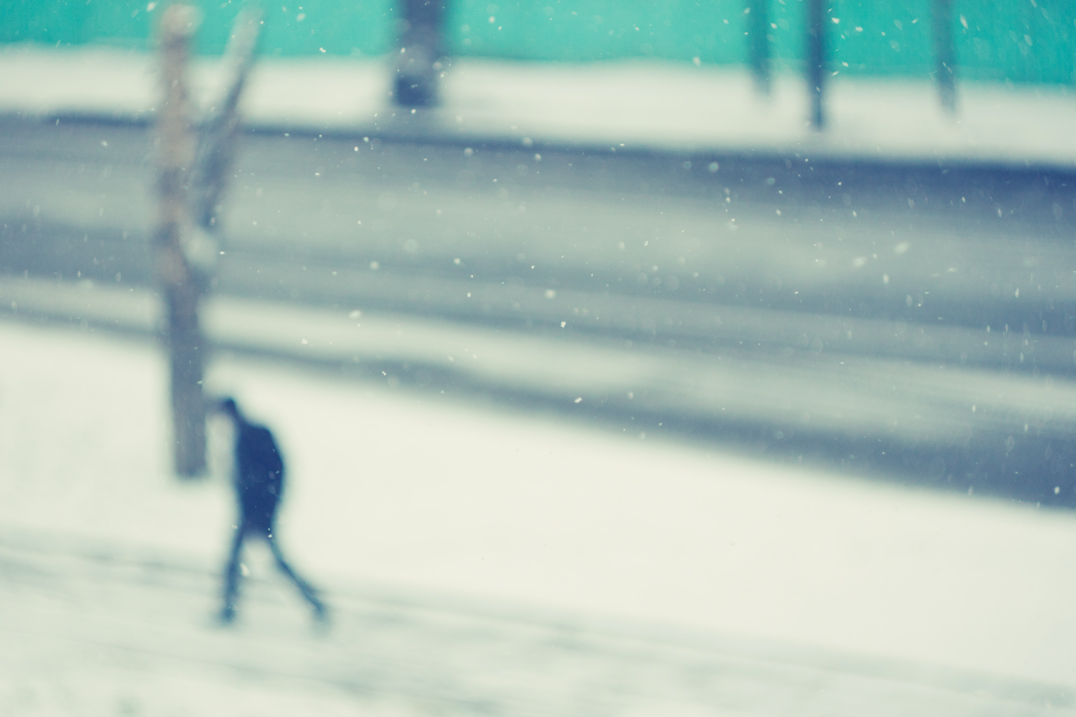 A blurry photo of a person walking in snow on the side of a road in Tomsk