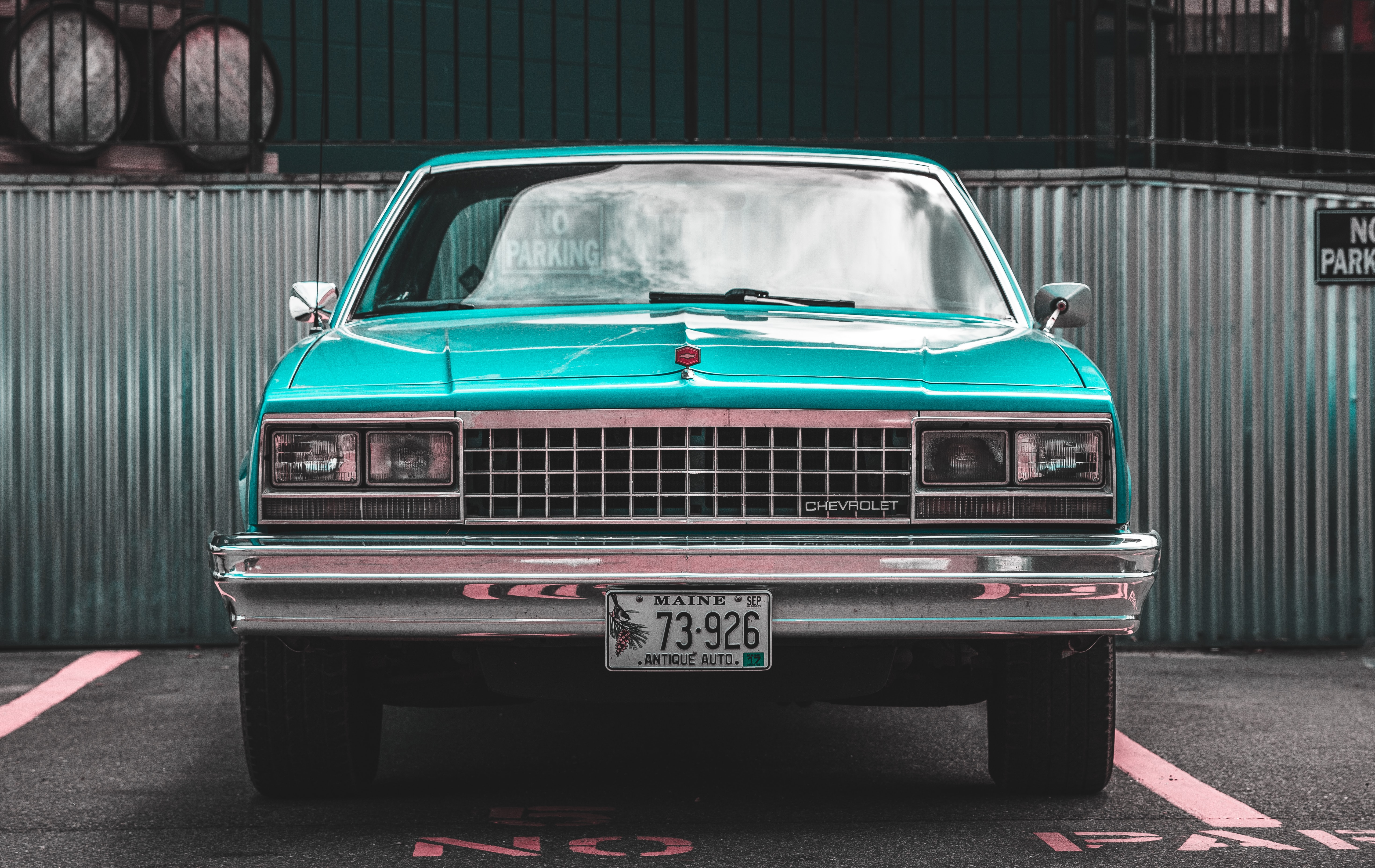 An aquamarine-colored vintage car in a parking lot.