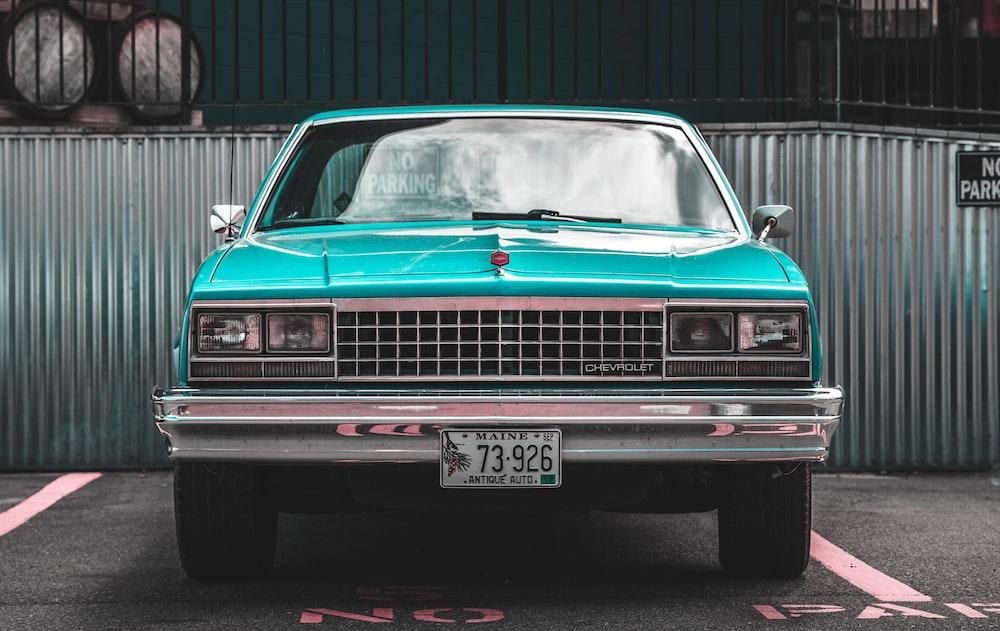 teal Chevrolet car parked on asphalt road near trailers