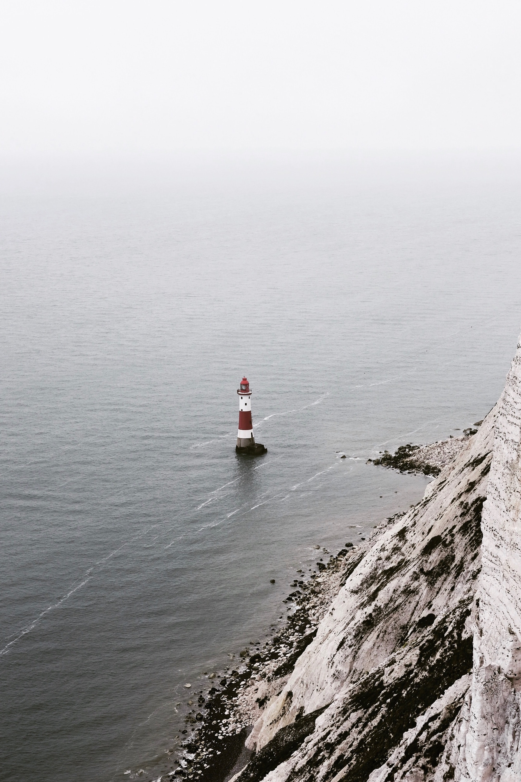 white and red lighthouse beside body of water