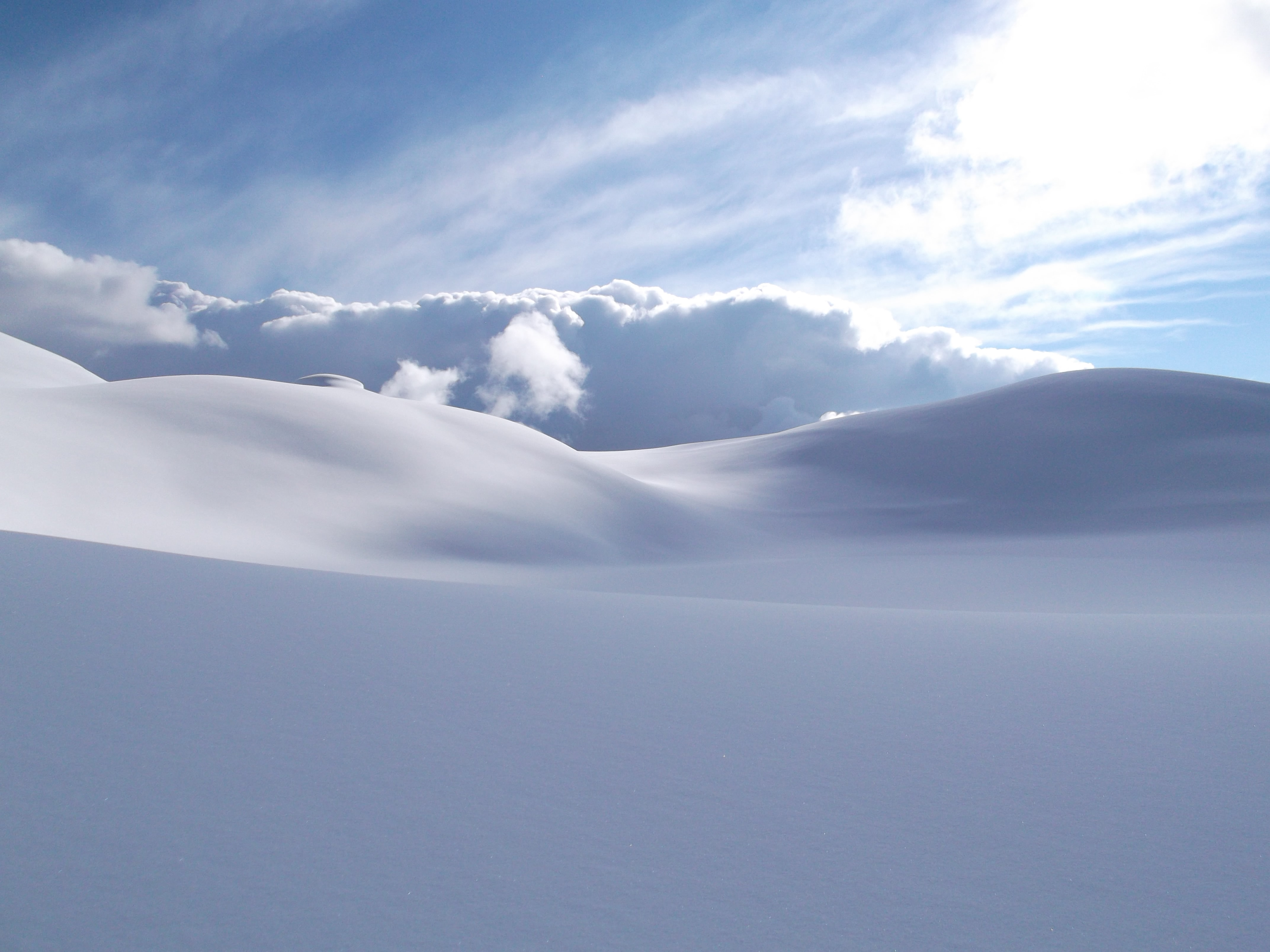 A cloudscape photograph from heavily snow covered mountains