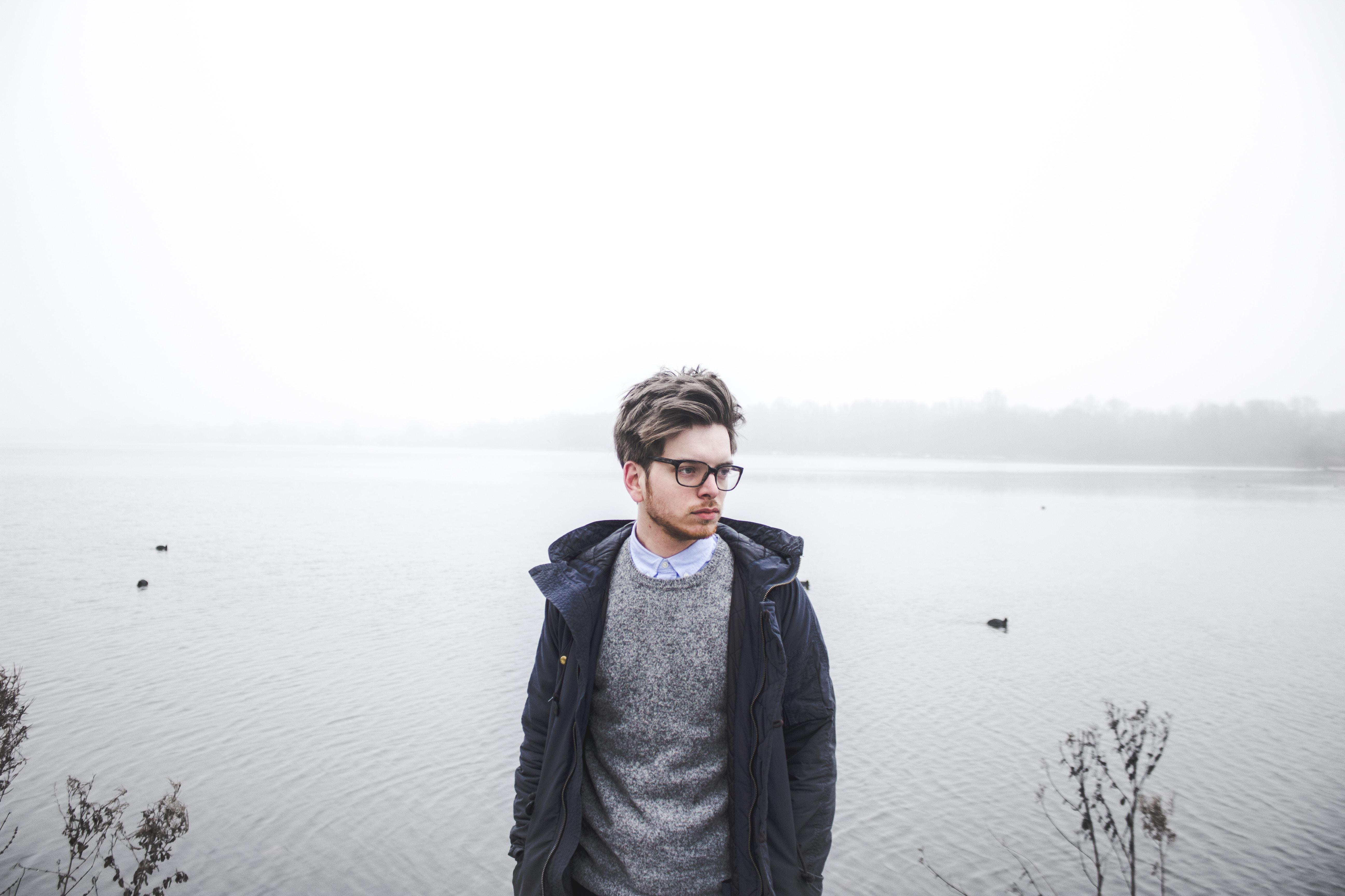 man wearing black jacket standing near body of water
