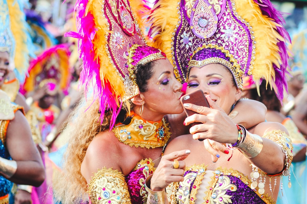 Two women Carnival dancers pose for a selfie as one kisses other on the cheek.