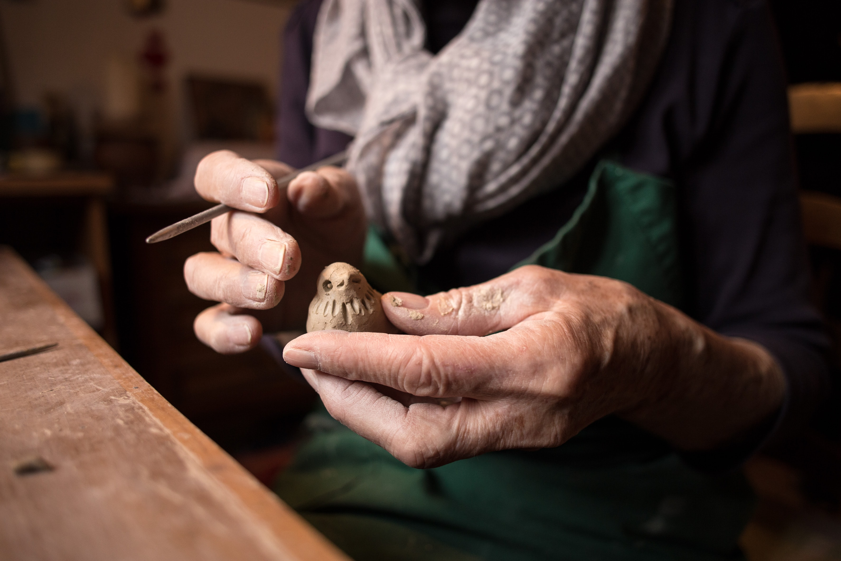 An elderly person carving a small bird out of wood