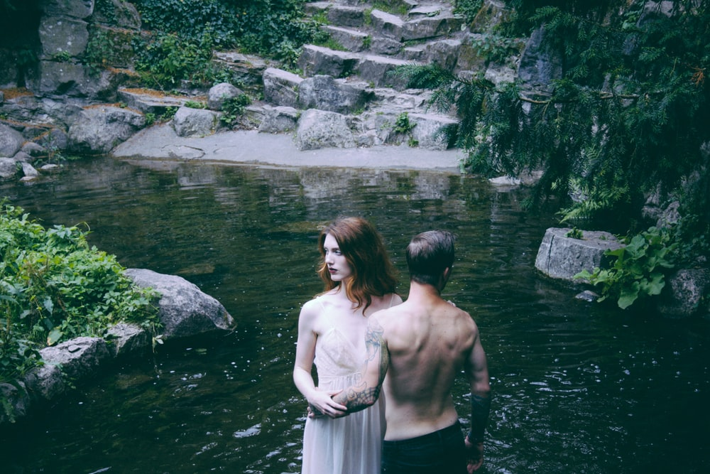 man and woman standing on body of water beside green leafed trees