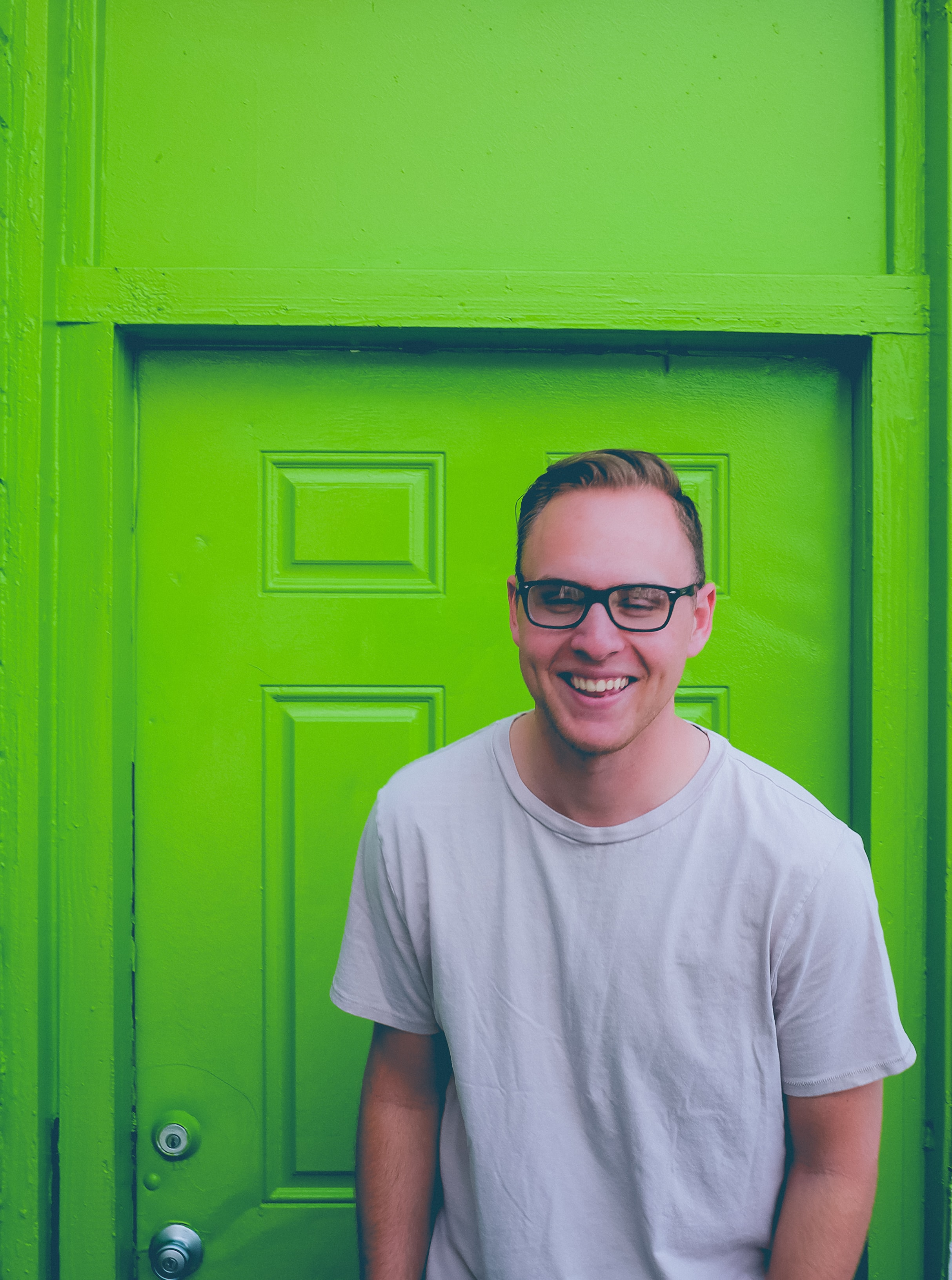 A man wearing glasses, smiling while standing in front of a green door.