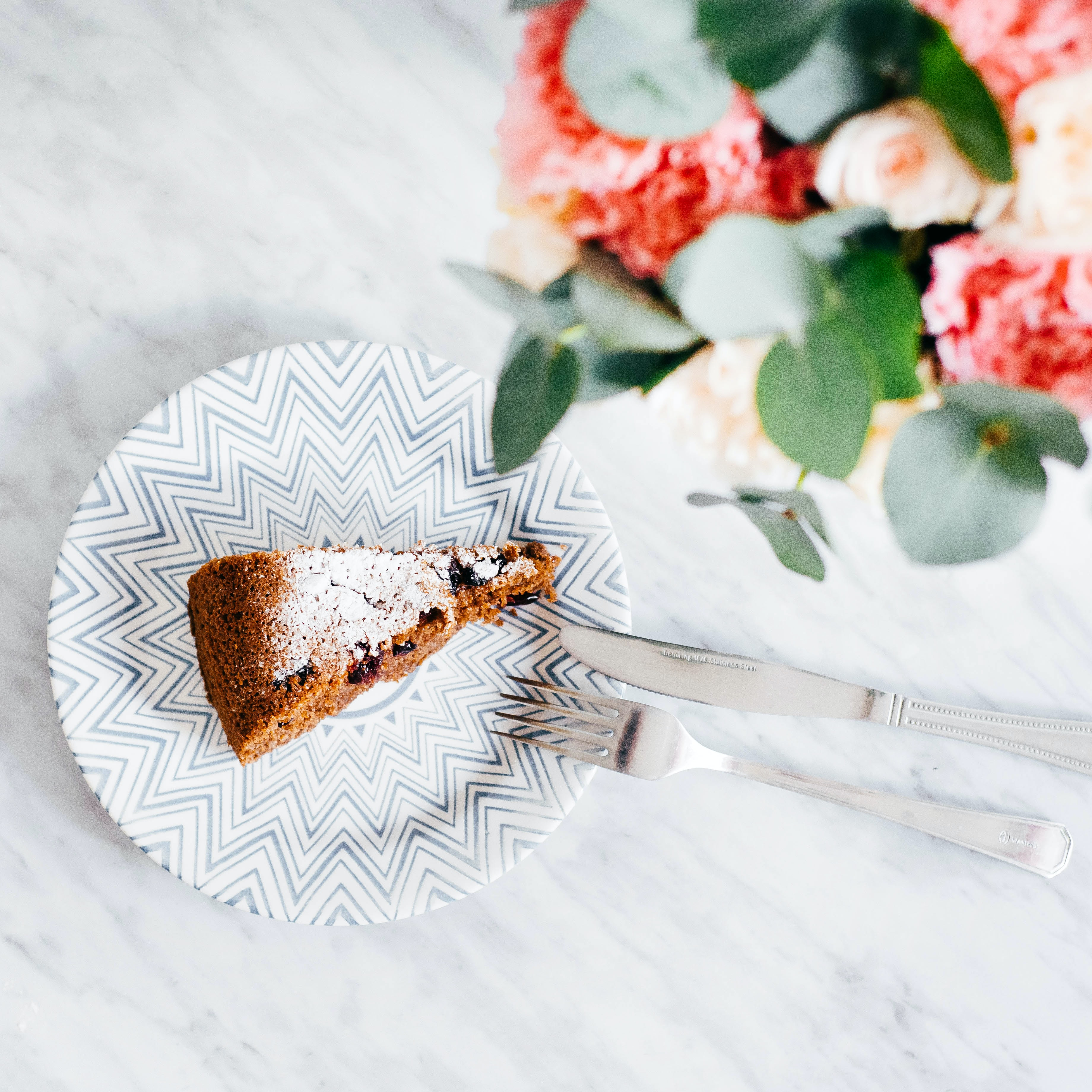 An overhead shot of a slice of cake on a plate next to a floral bouquet