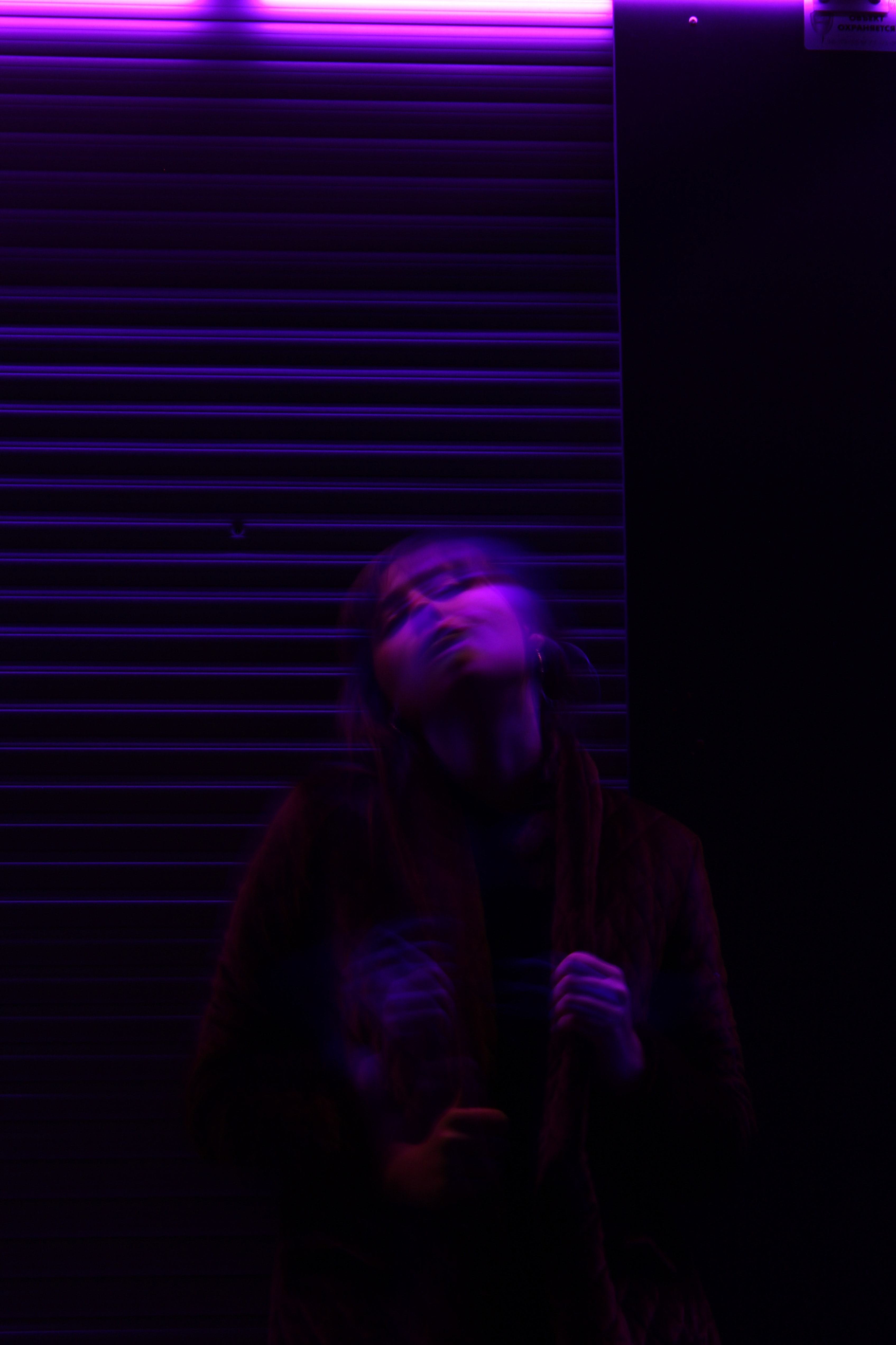 A motion blur shot of a young woman under purple lighting in Kaliningrad.