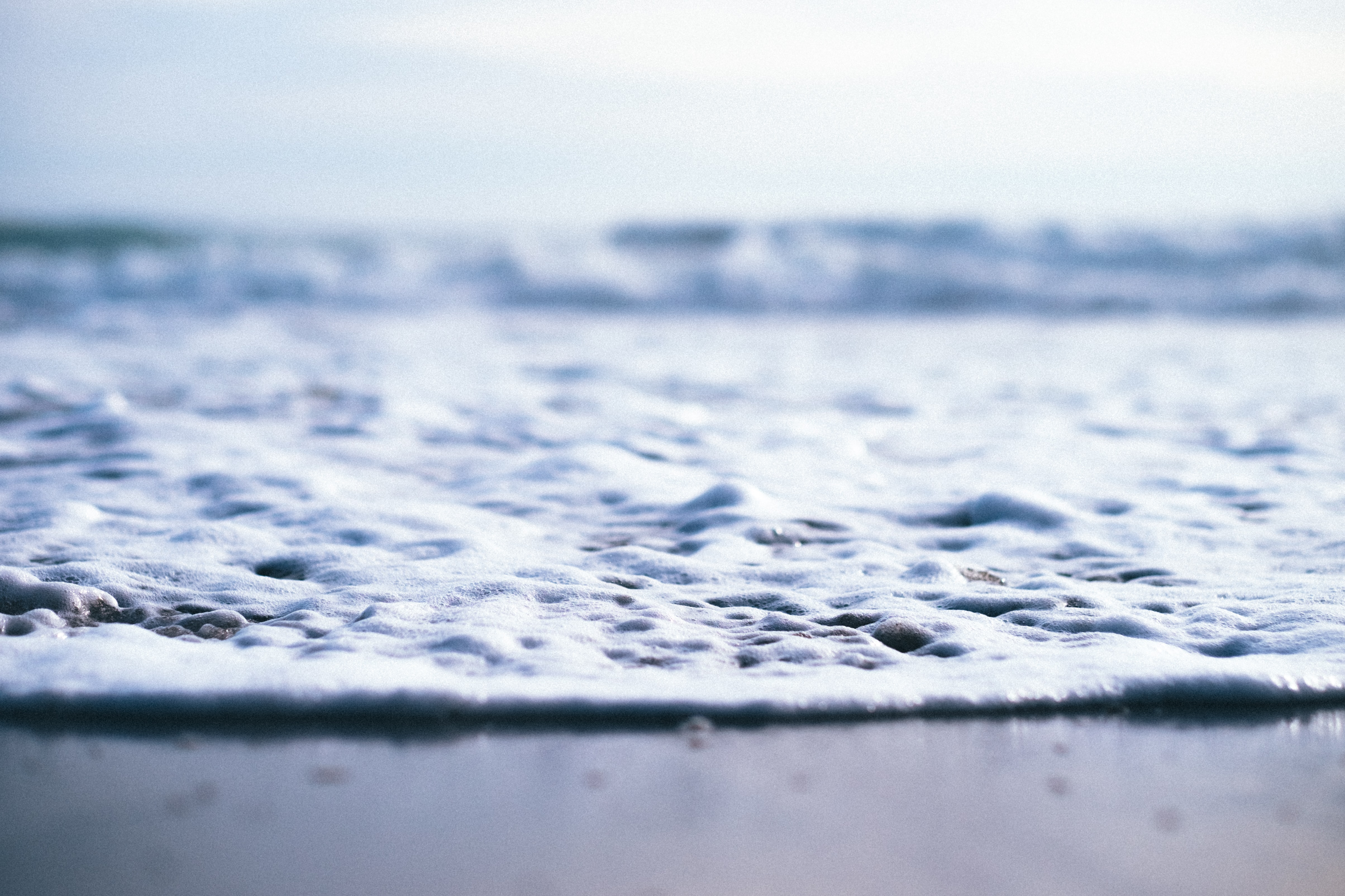 Closeup shot of the sand and sea as the water foams up taken in Sunset State Beach