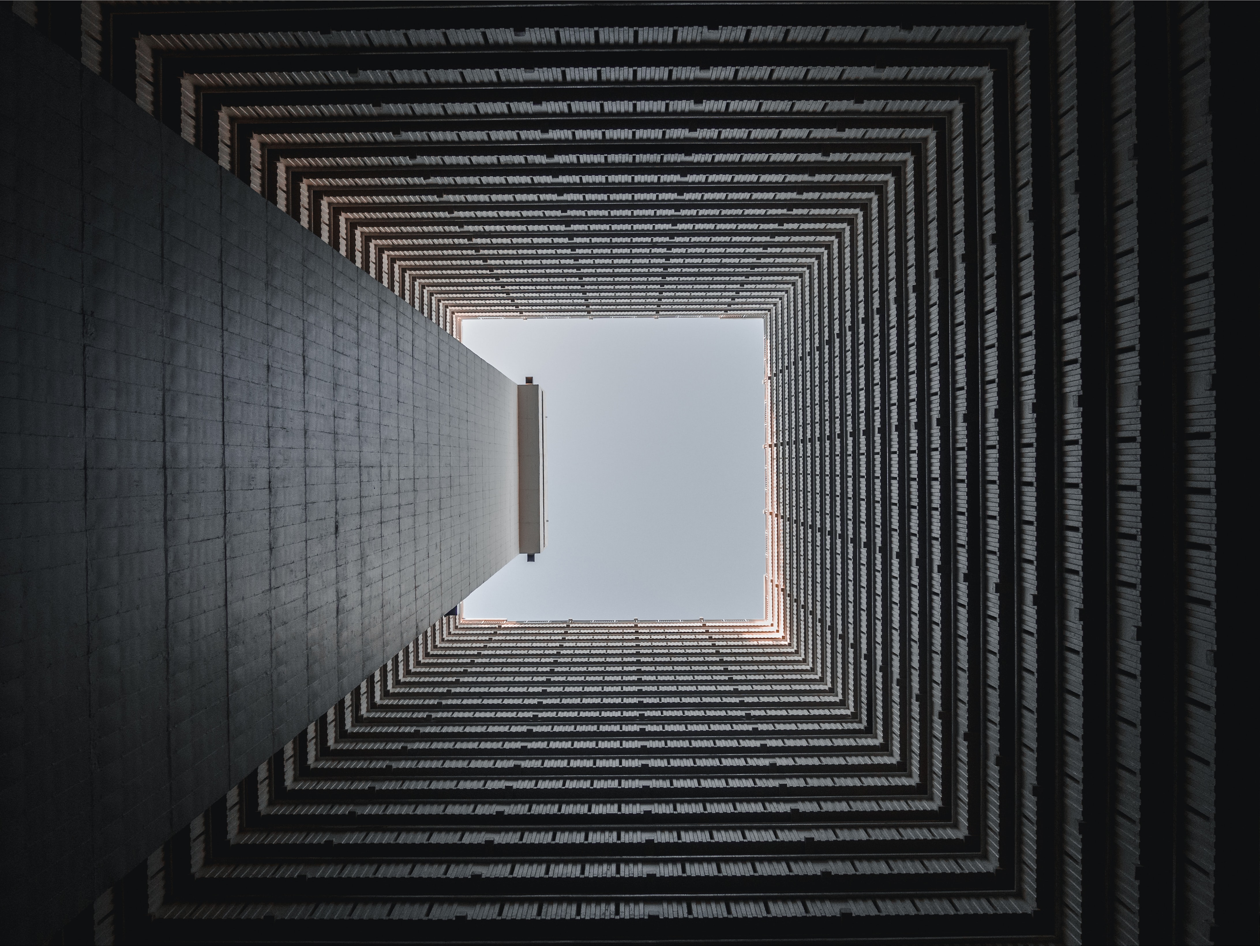 View from the bottom of a square well on the blue sky above