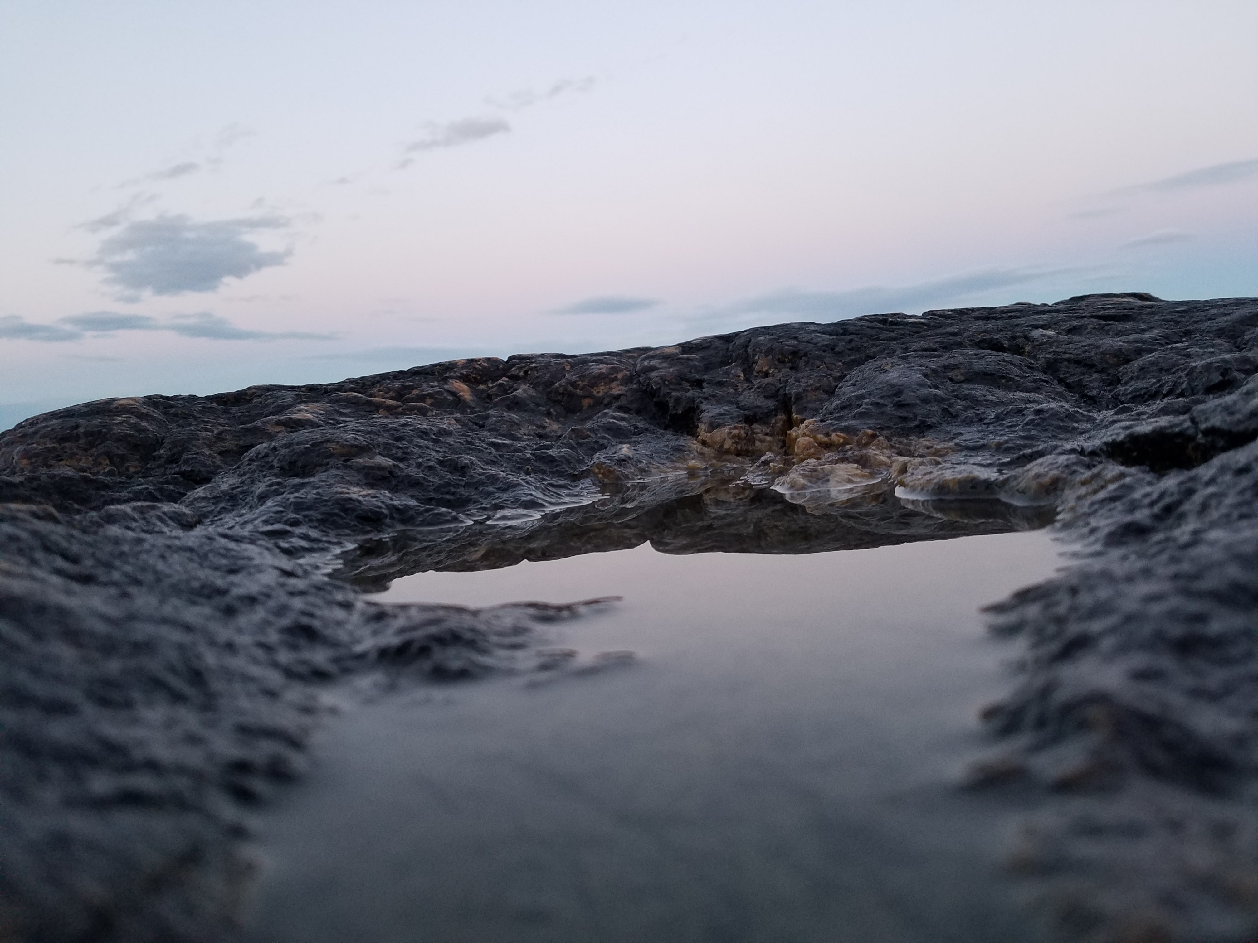 body of water near rock formation at night
