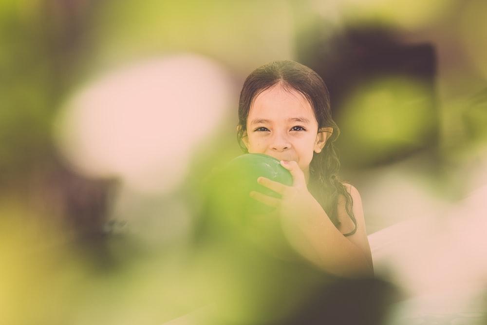 girl blowing green balloon