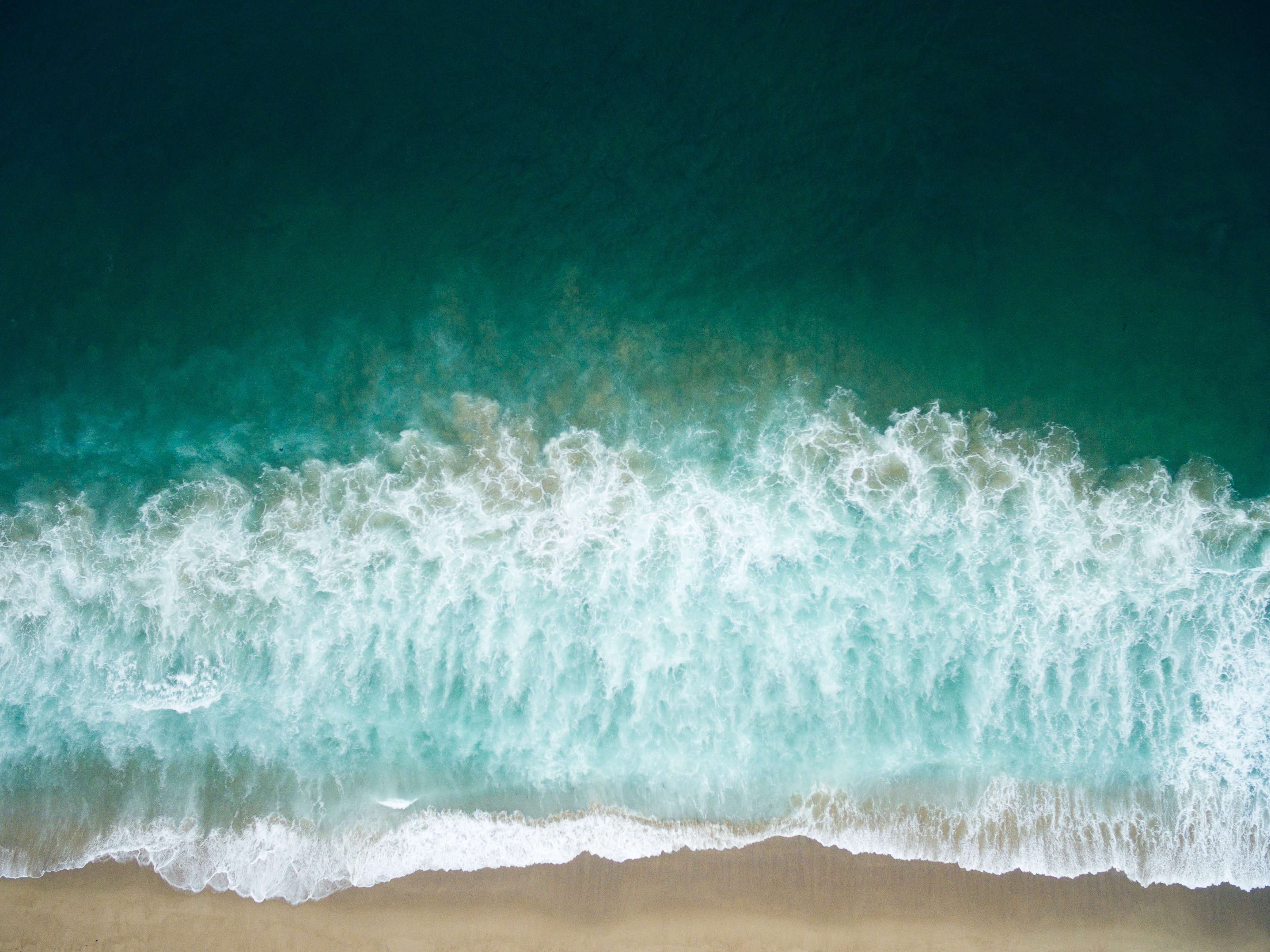 Drone aerial view of the waves washing on the Redondo sand beach