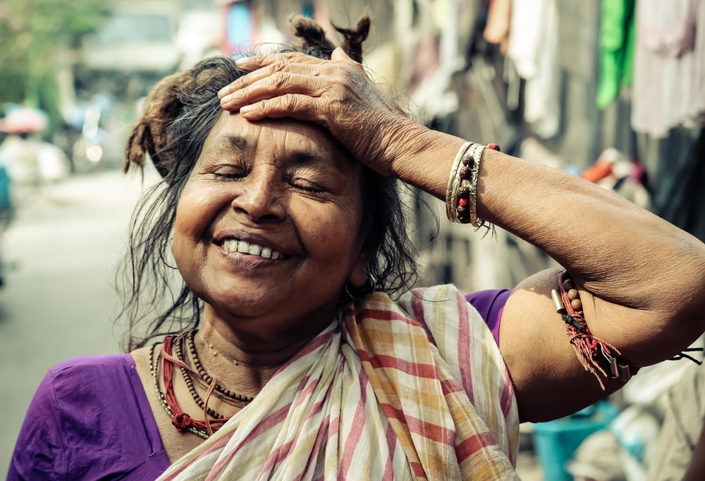 closeup photo of smiling woman holding her forehead