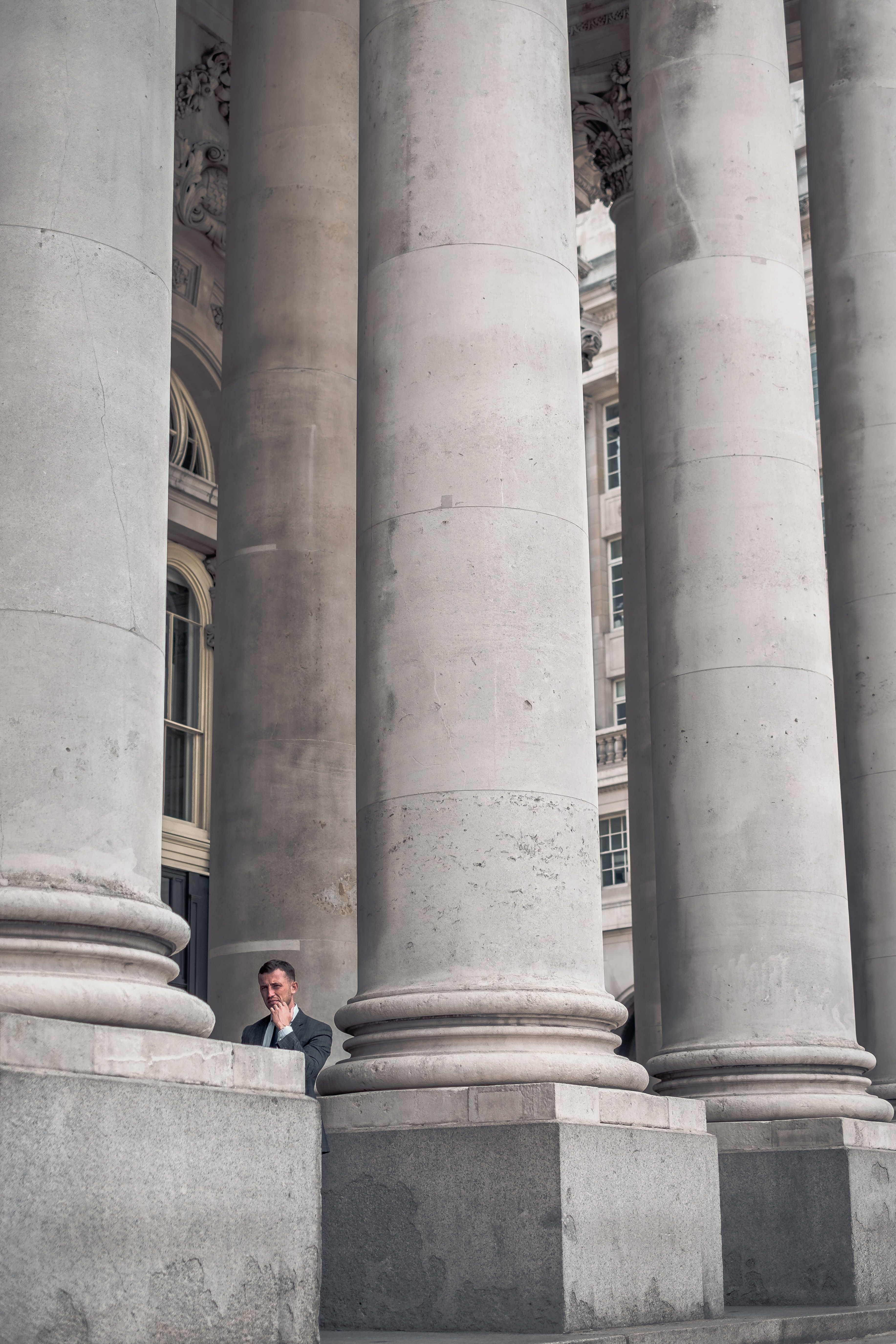 A man in a suit standing near the tall columns at the entrance to the London Stock Exchange