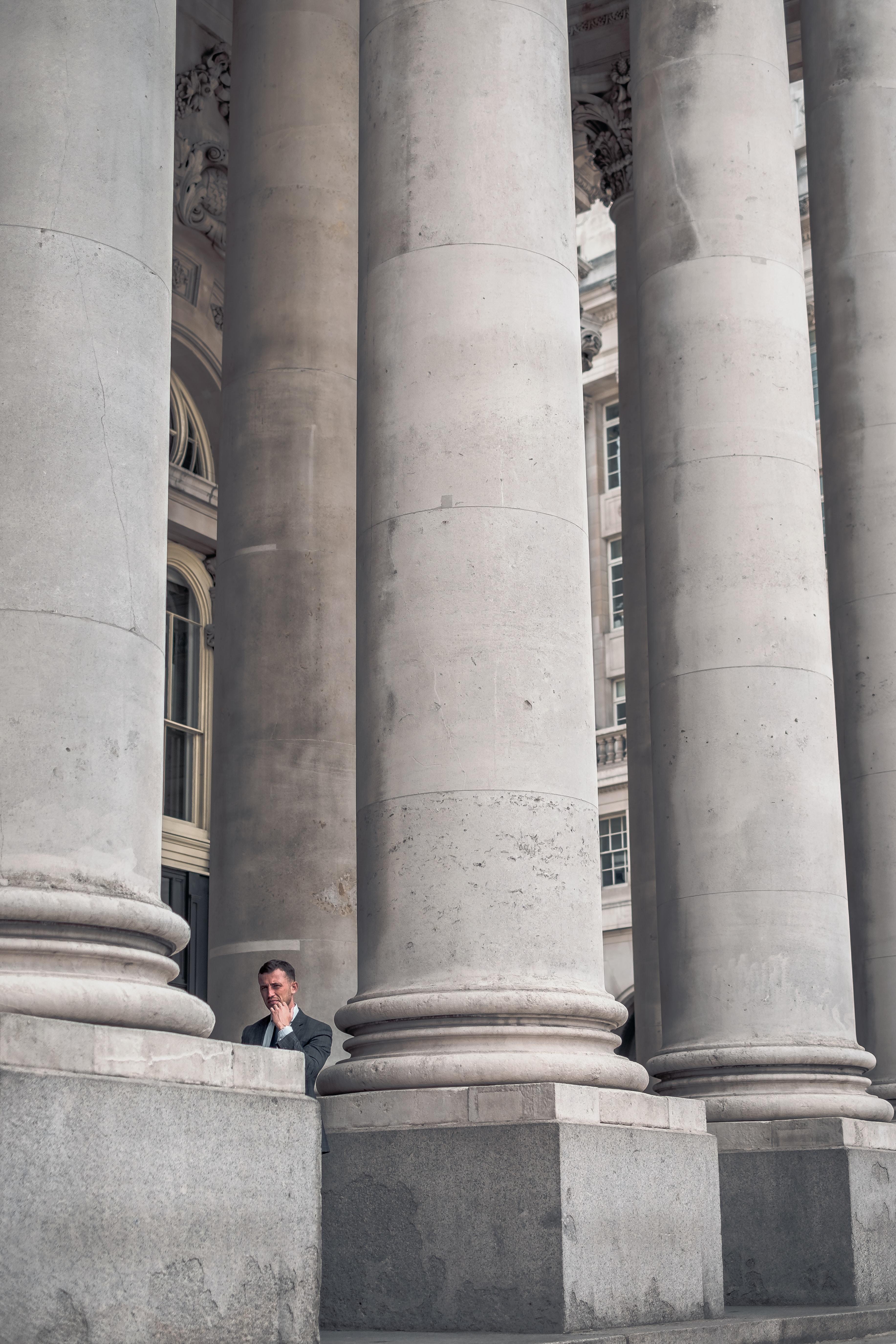 man standing beside gray concrete pillars
