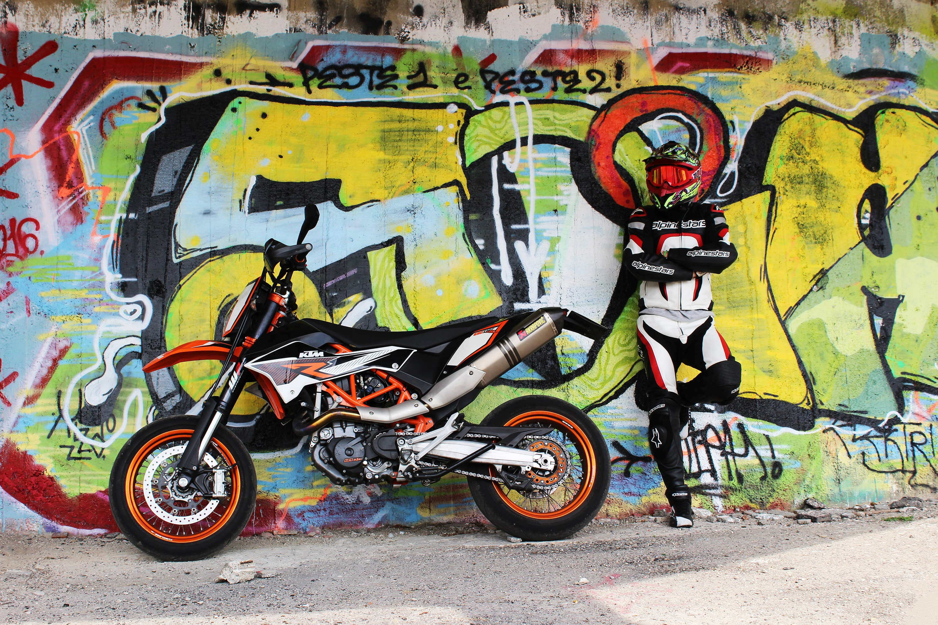 Motorbike and rider in crash helmet leaning against graffiti street art in Consonno