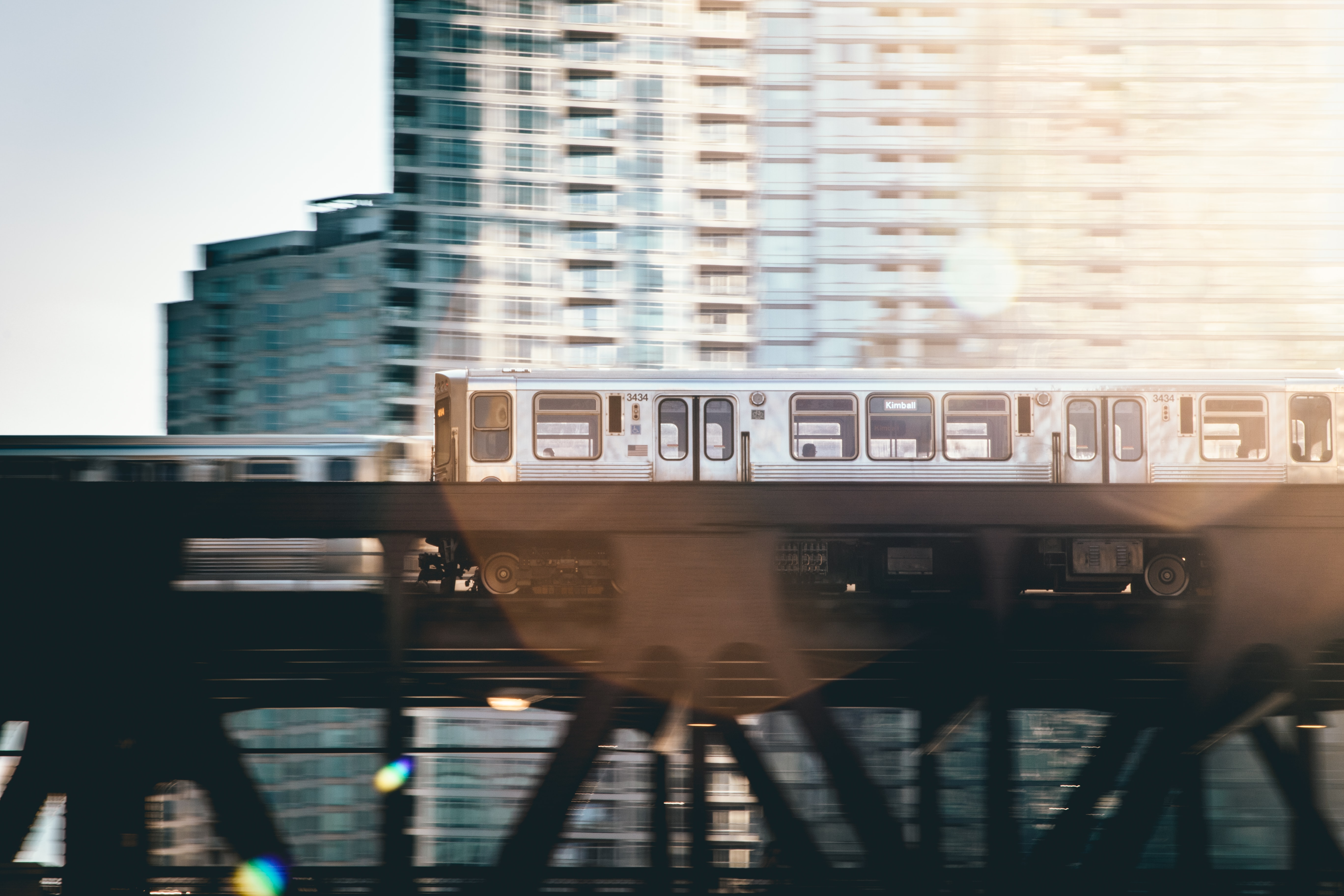 Wide angle shot of an elevated train speeding through the Chicago skyline.