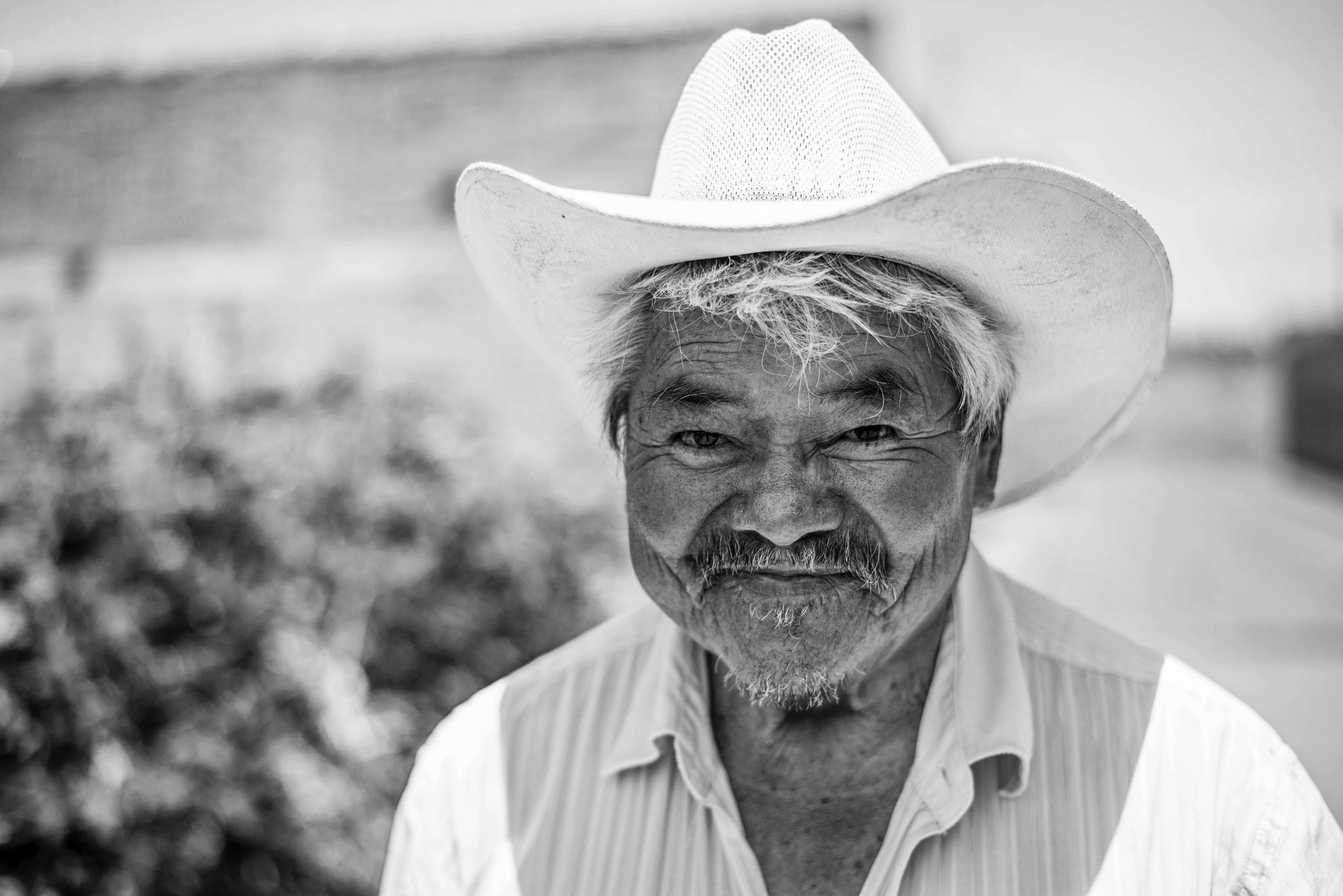 Black and white shot of older man in white cowboy hat in white shirt in daytime