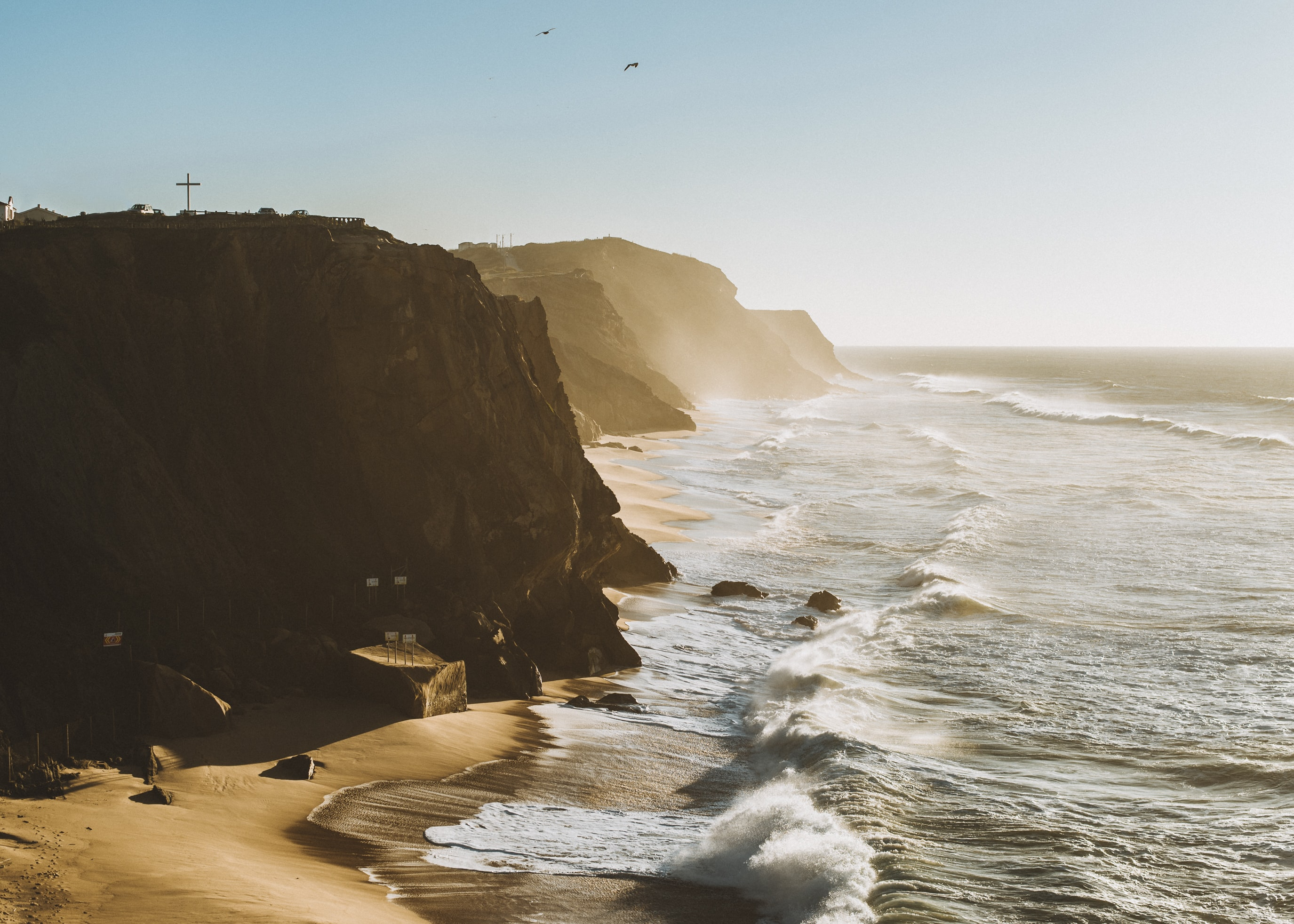 Ocean waves crashing on the sand beach with cliffs in Santa Cruz