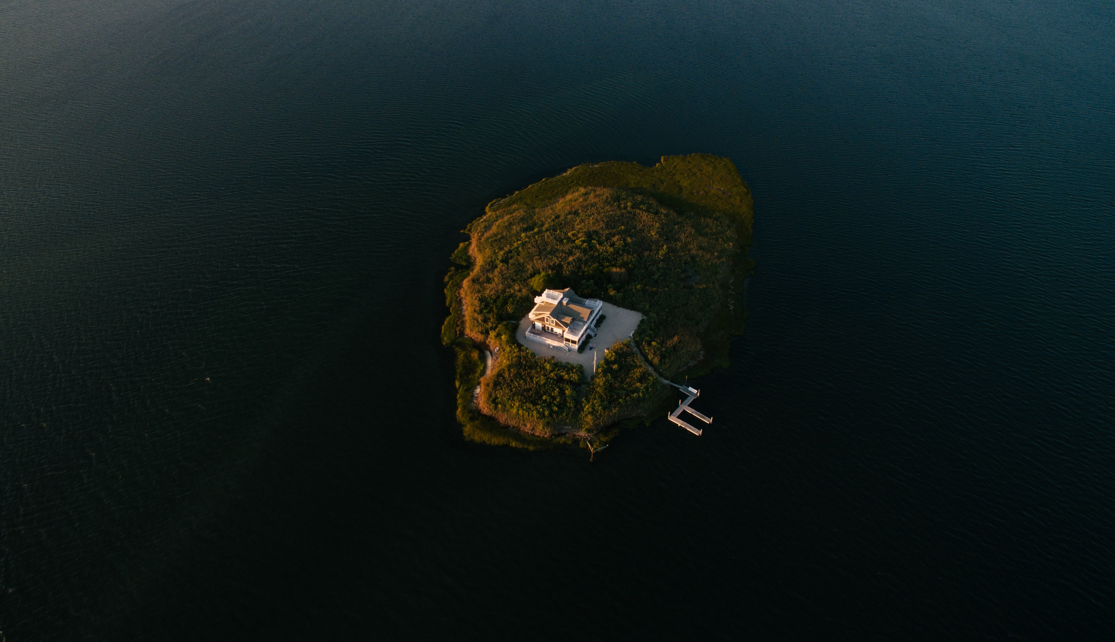 Drone aerial view of a white house with a dock on a small green island at Long Beach Island