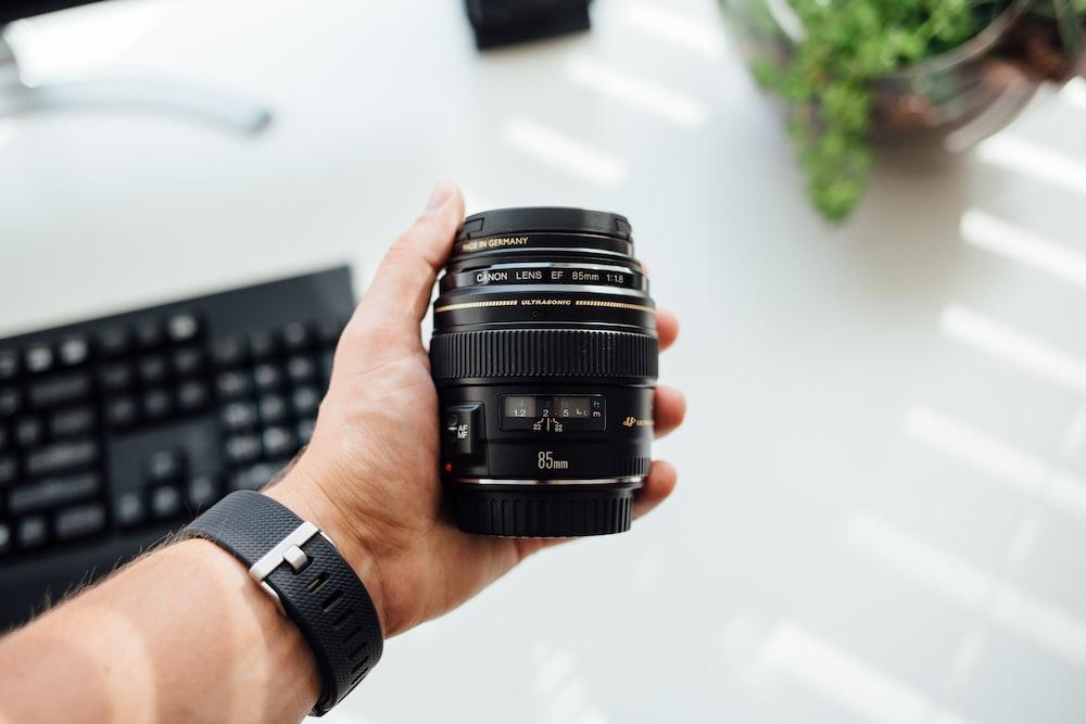person holding DSLR camera lens
