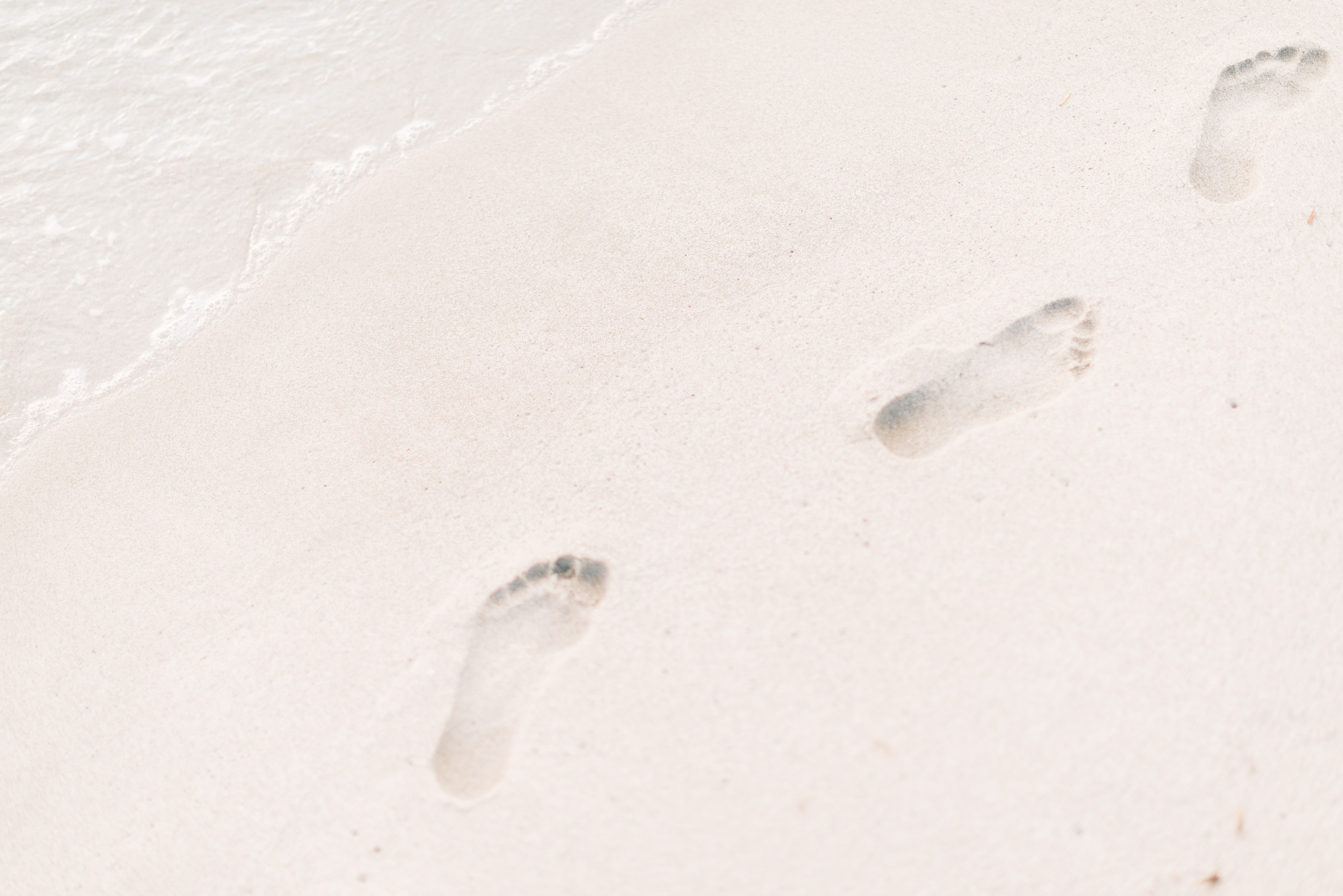 A close-up of footprints left by a person walking barefoot on a sandy beach