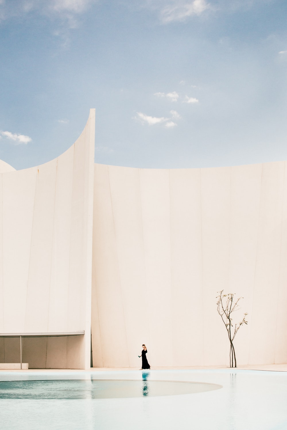 woman standing in front of white building